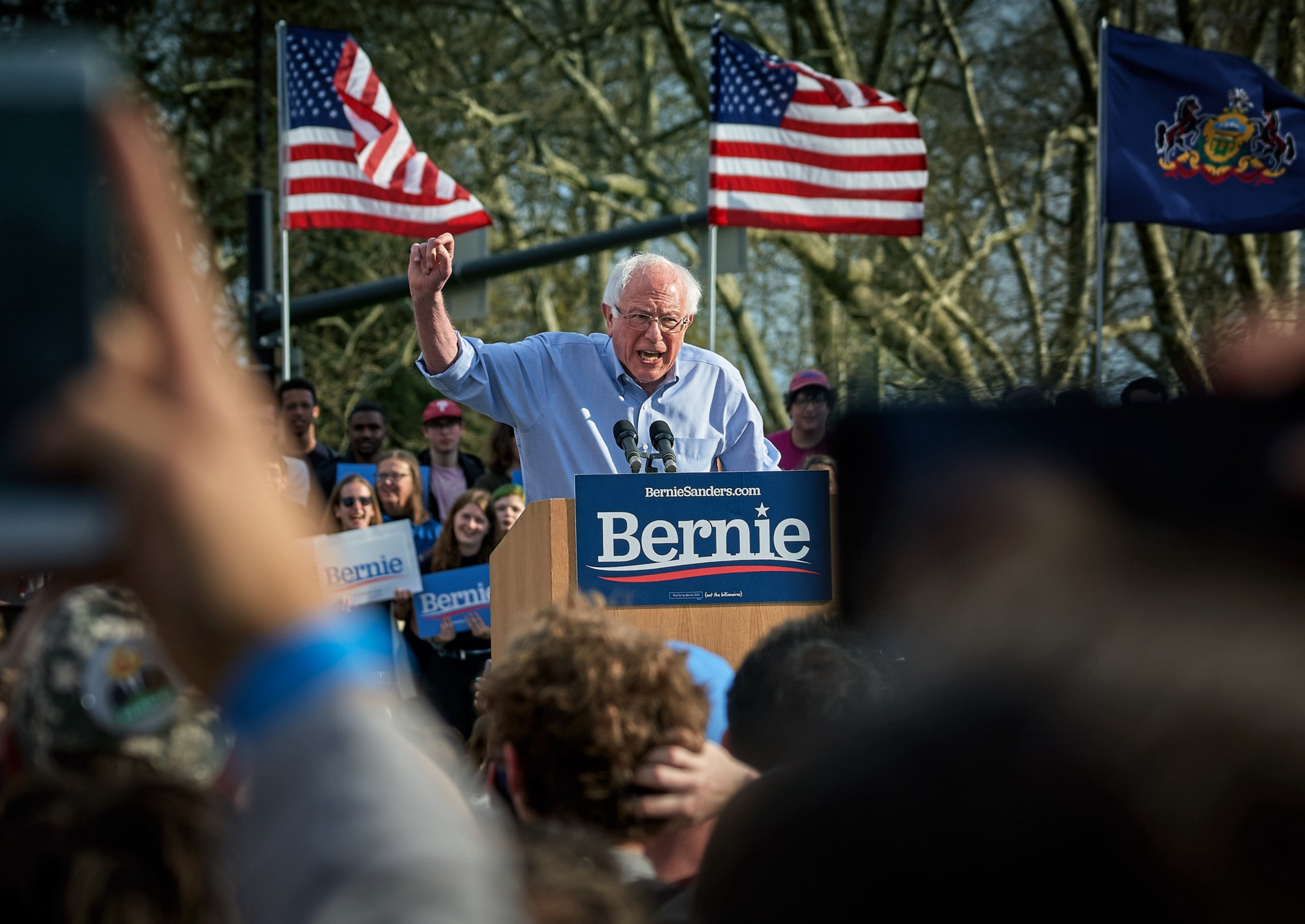 Bernie Sanders speaking at a podium outside, with American flags behind him