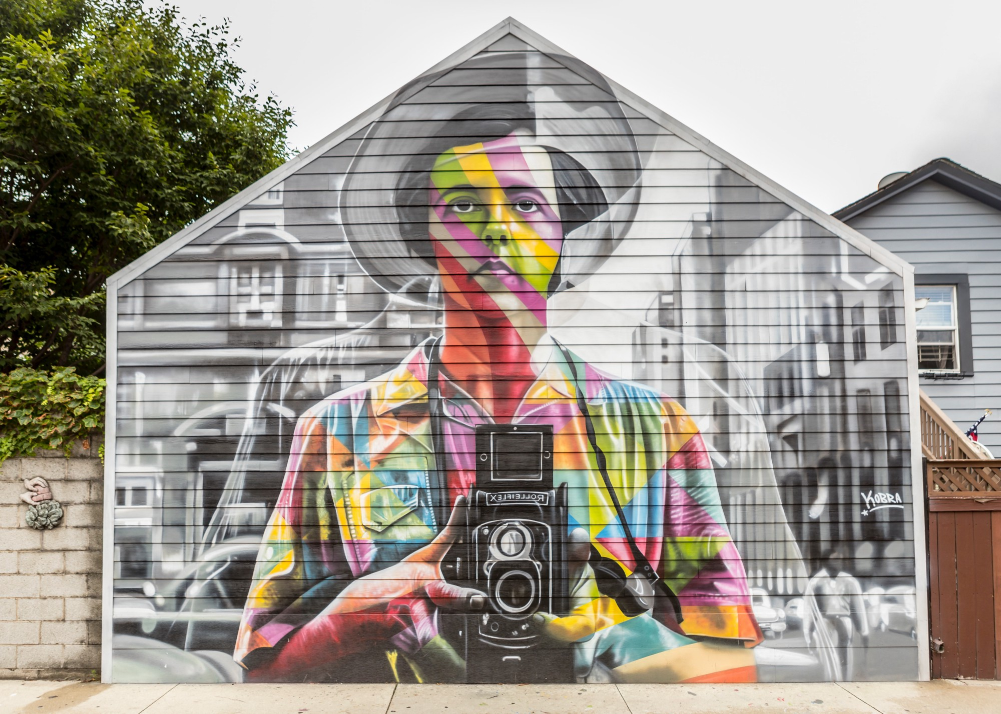 A mural of a person holding a camera.