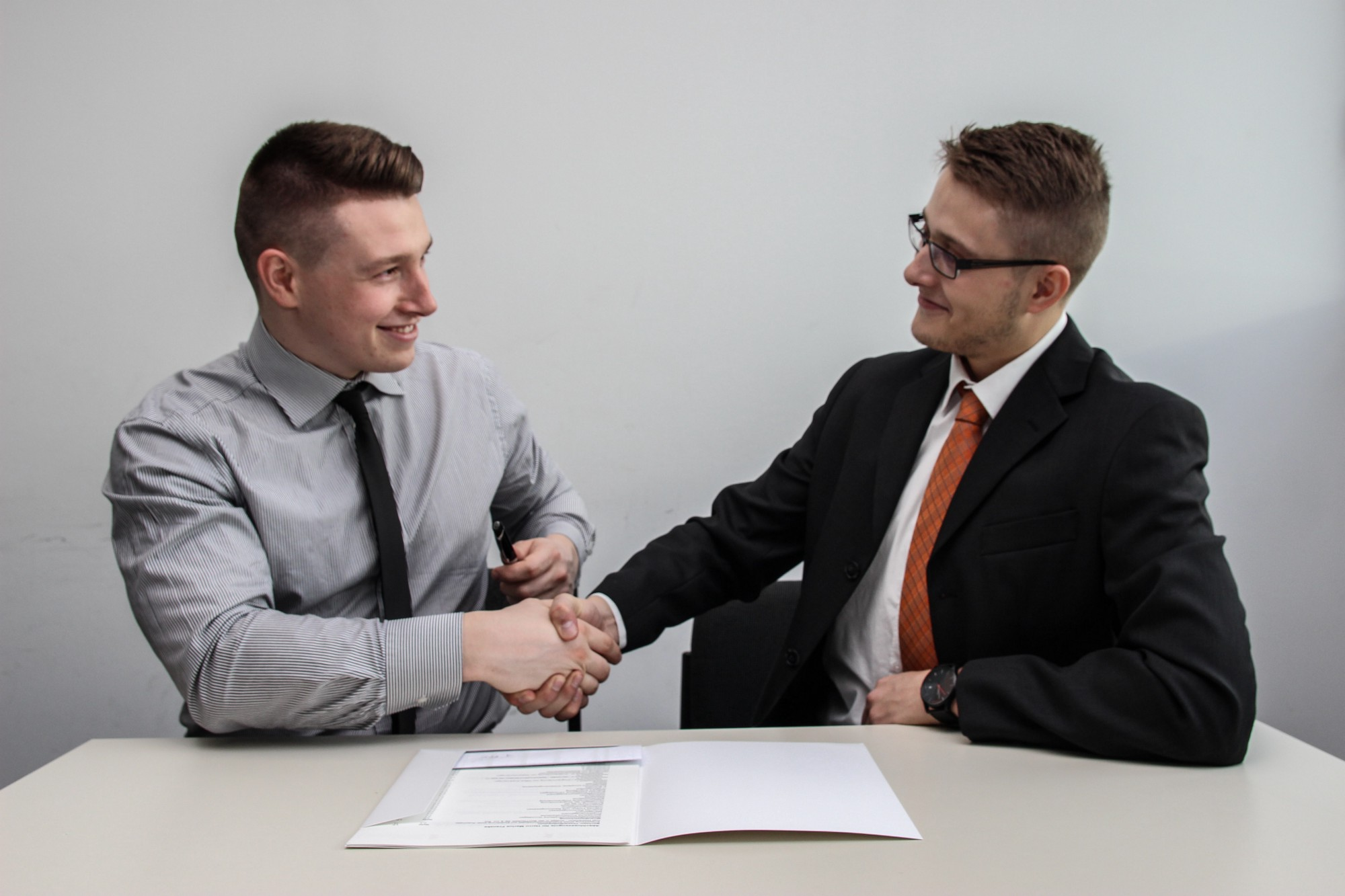 Two young men in business suits shaking hands