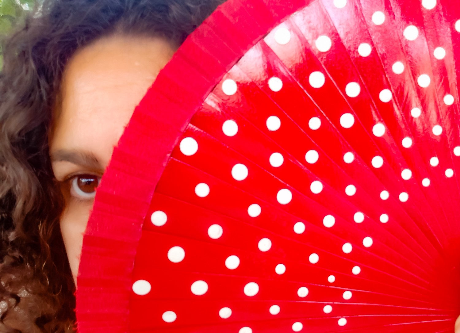 Image of the author partially covering her face to reveal only the left eye looking straight, while hiding behind a Spanish red fan. Her (my) features are Mediterranean, brown eyes, tan skin, and brown curly hair.