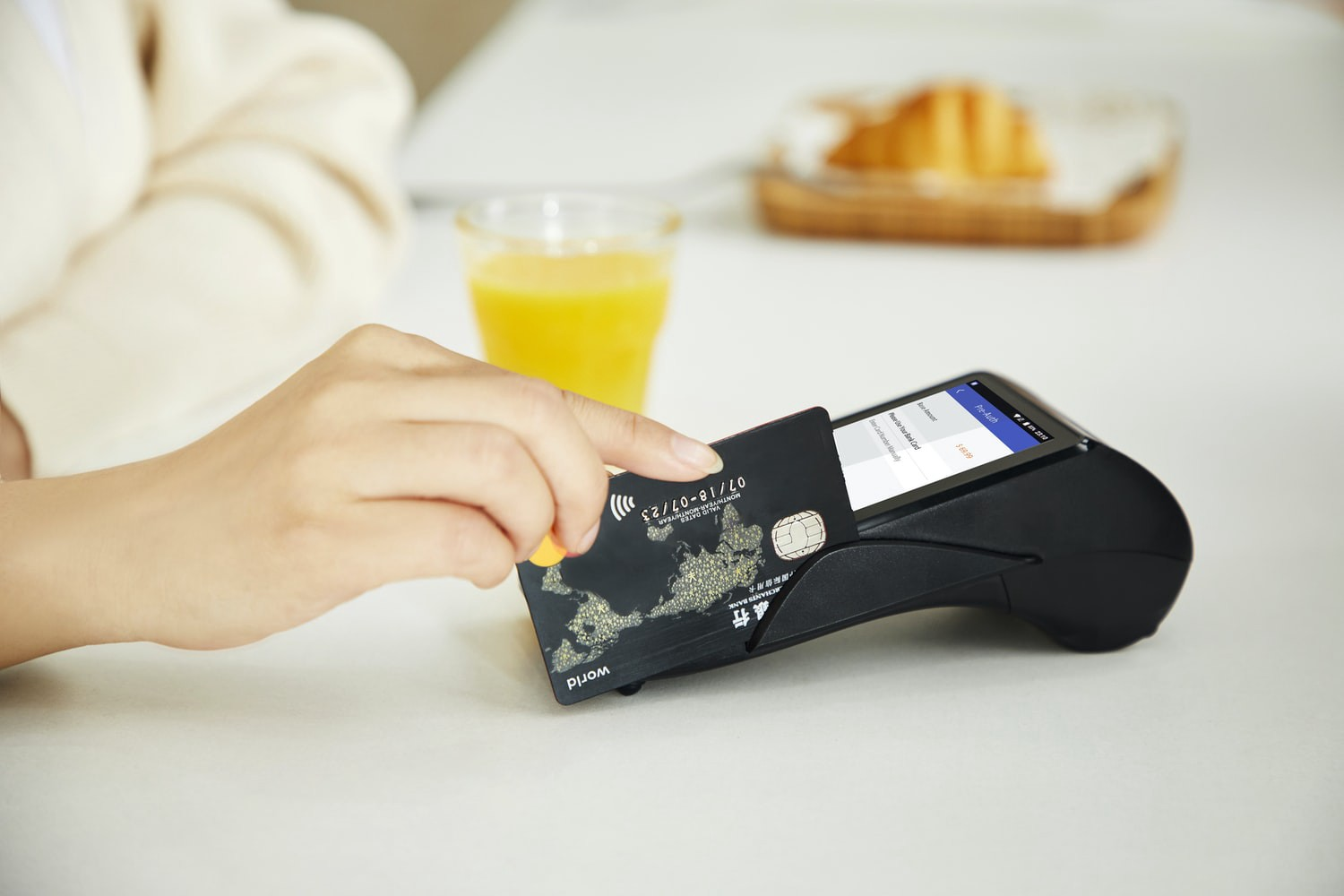 A hand sliding a credit card through a reader.