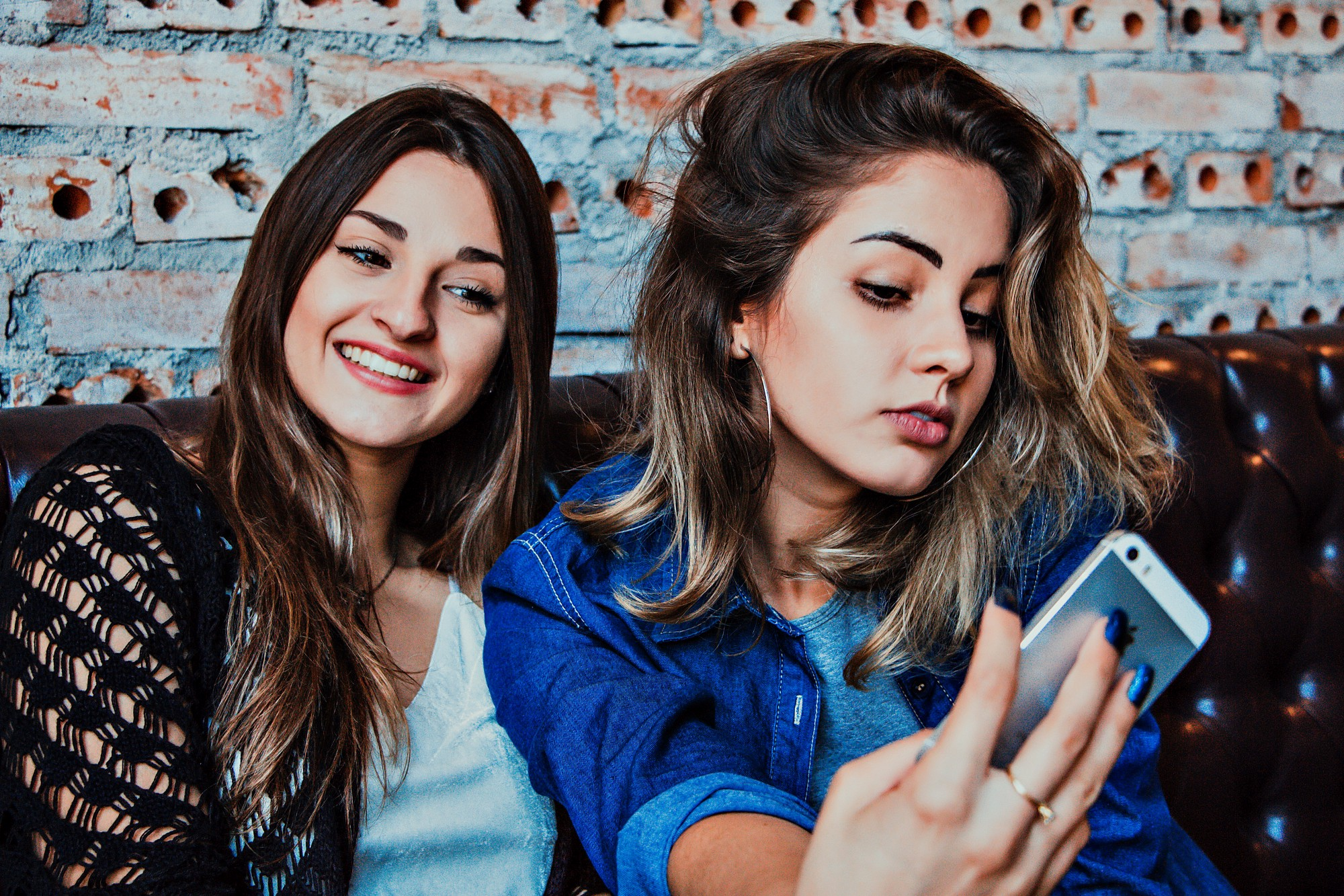 Two girls taking a selfie together. One smiling, one looking sly.