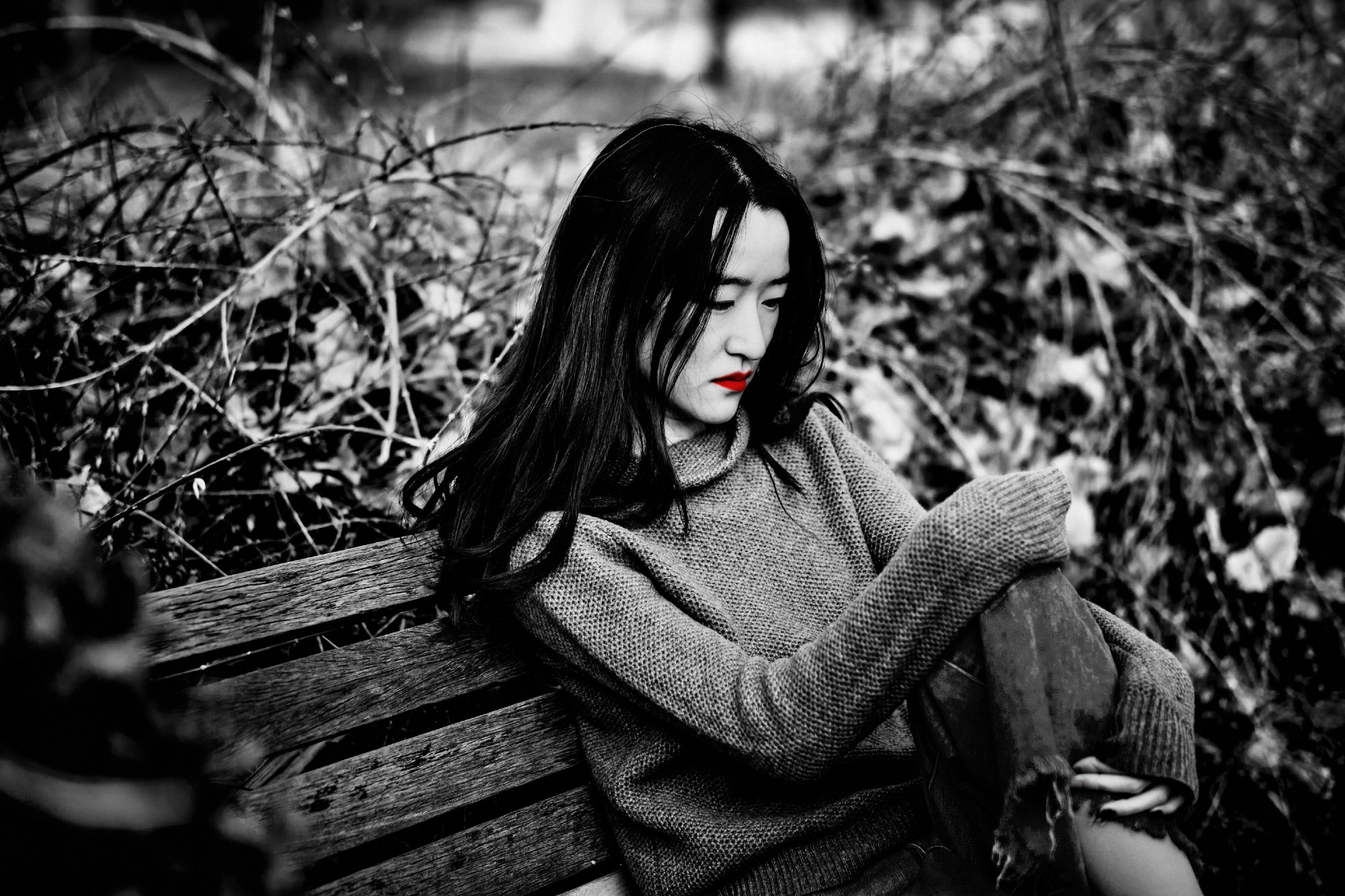 A black and white image of a sad Asian woman on a park bench. Her lips are red.
