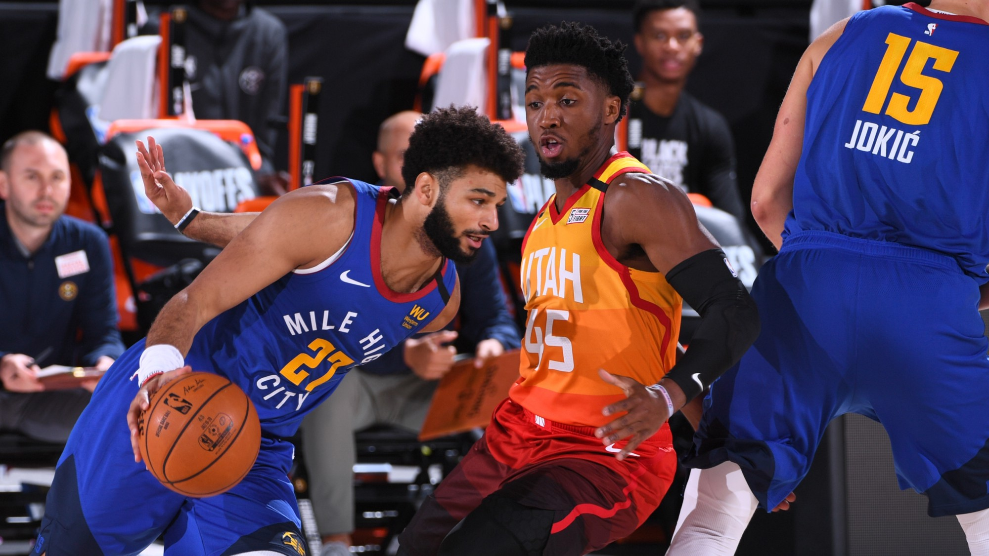 Two basketball players (Jamal Murray (left) and Donovan Mitchell (right)) facing off