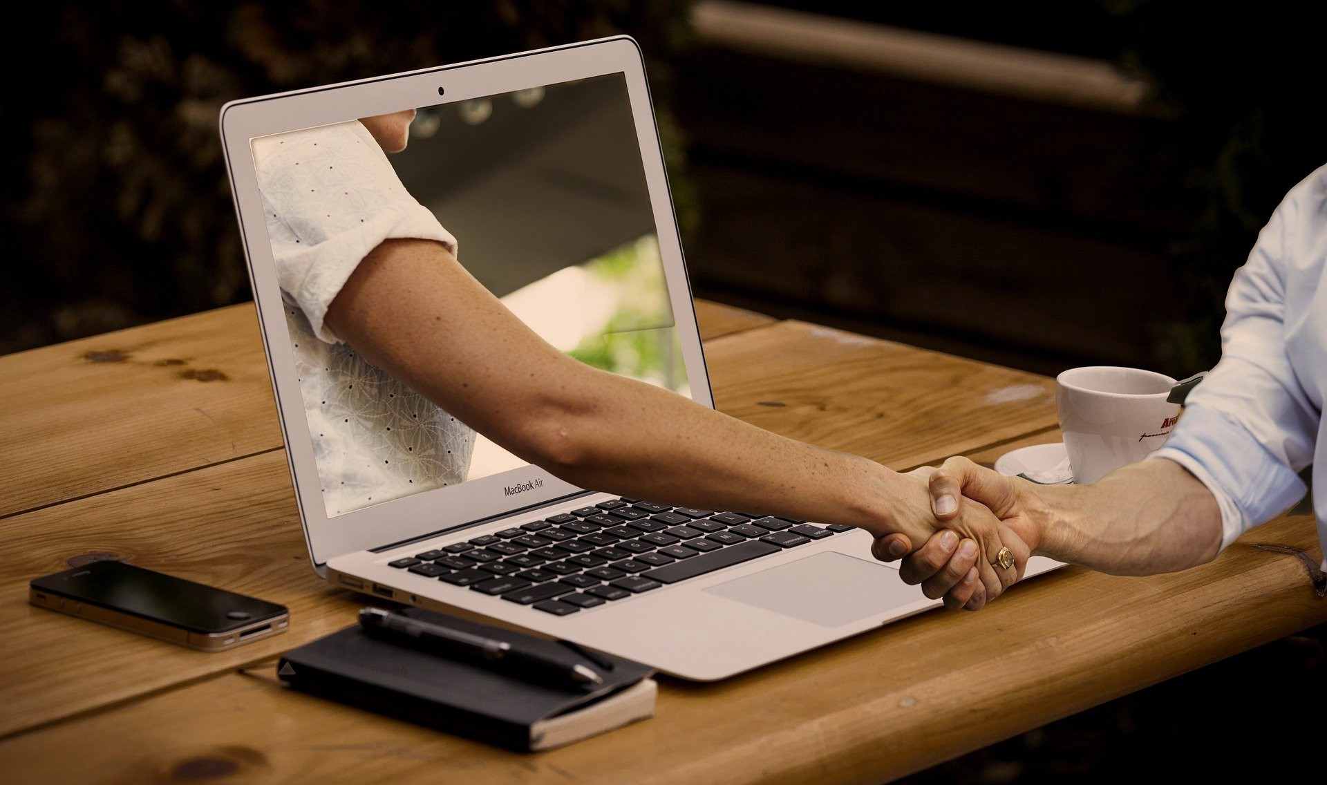Hiring web developers is not always a good idea. Photo: a hand extending out of a laptop screen.
