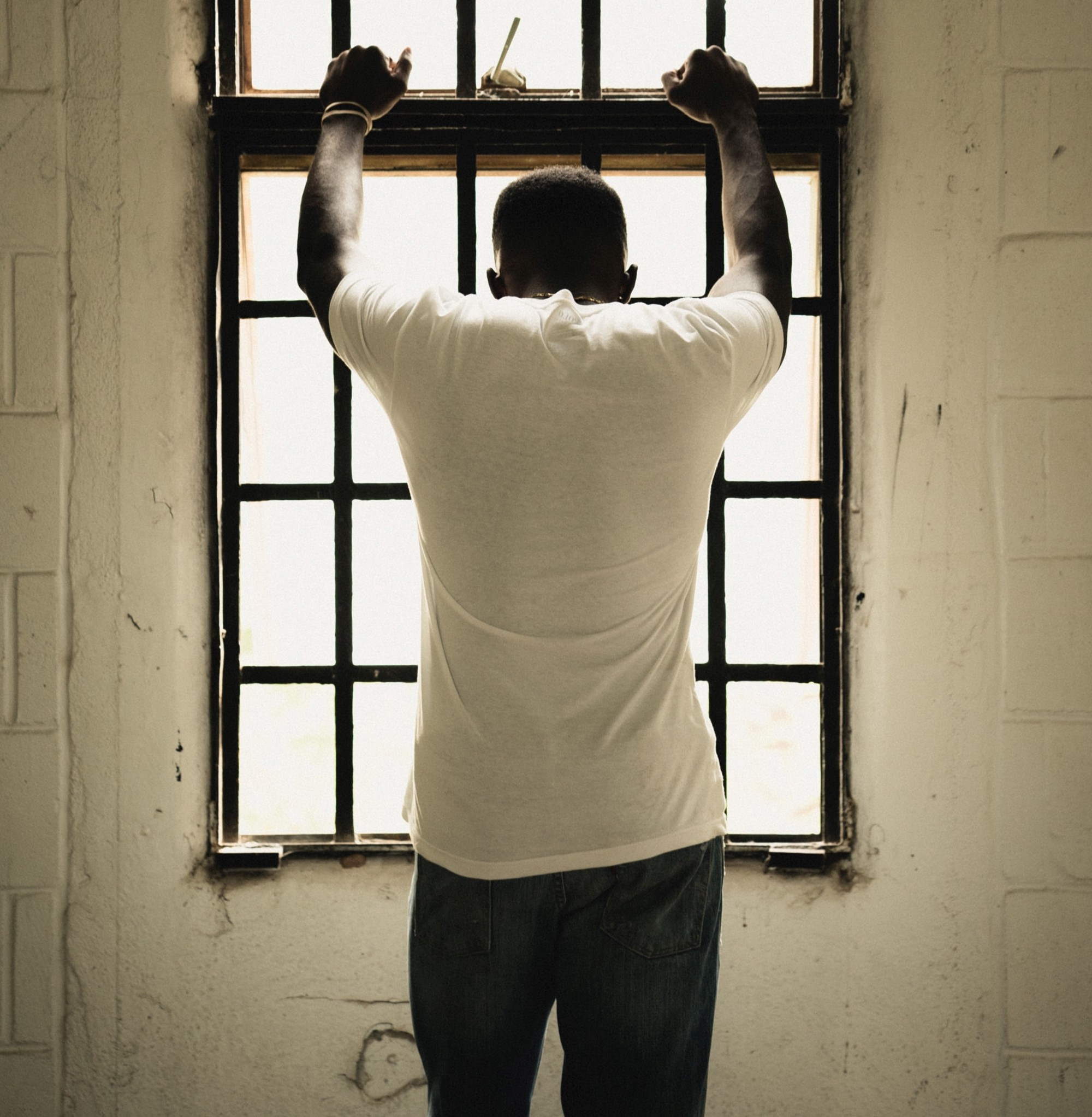 a sad man standing in front of a window