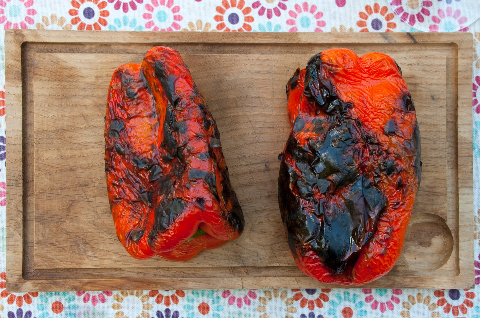 Charred red peppers on a wooden board.