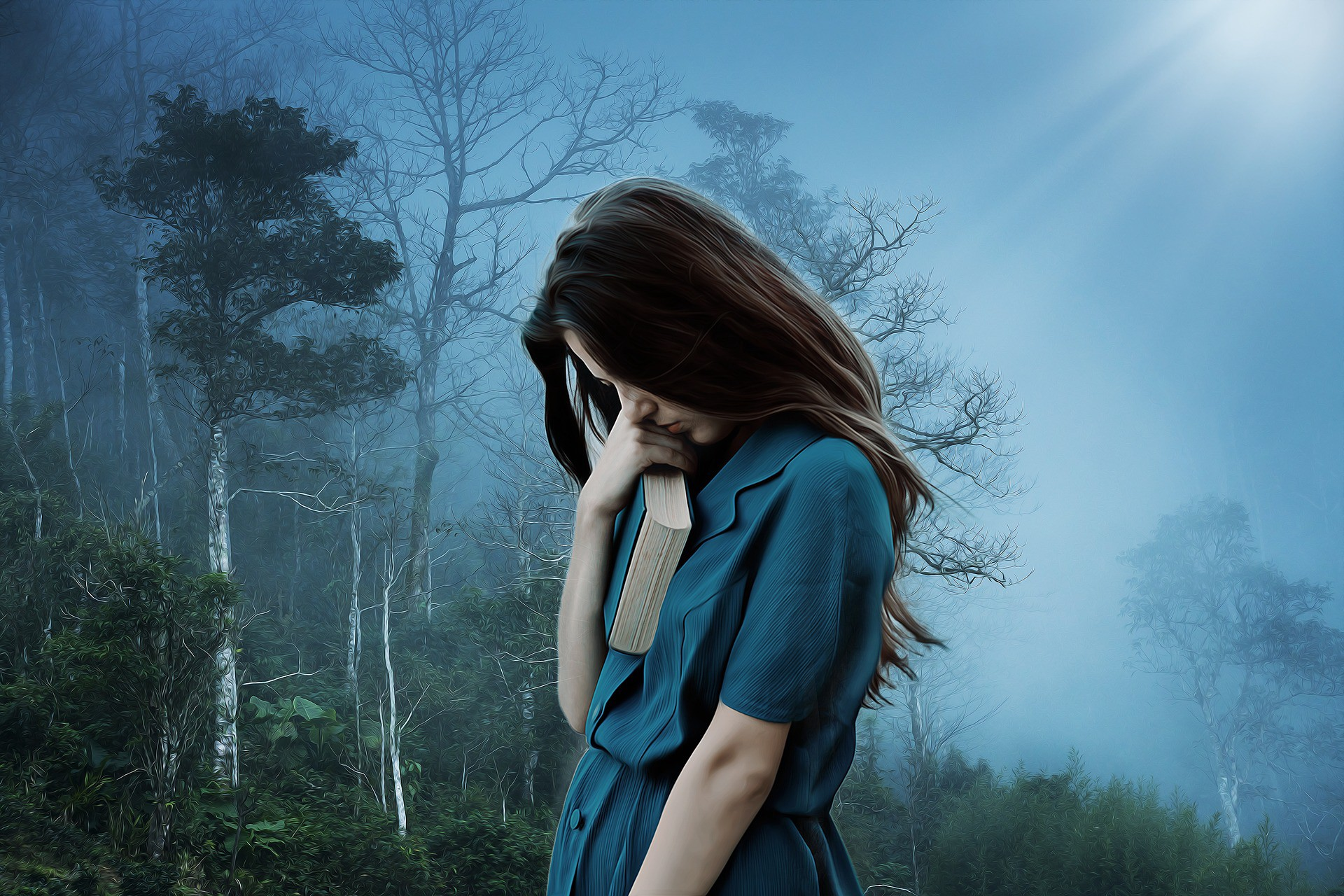 A woman looking down with her face obscured by hair. She is holding a book. The background is a dark and foggy forest.