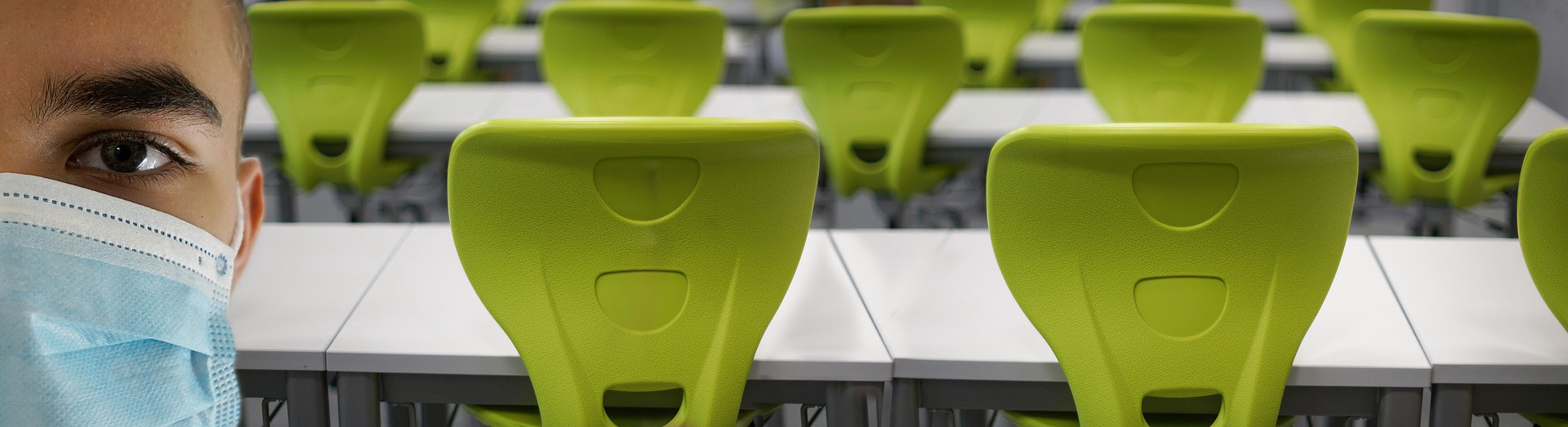 Rows of green chairs behind a person wearing a mask