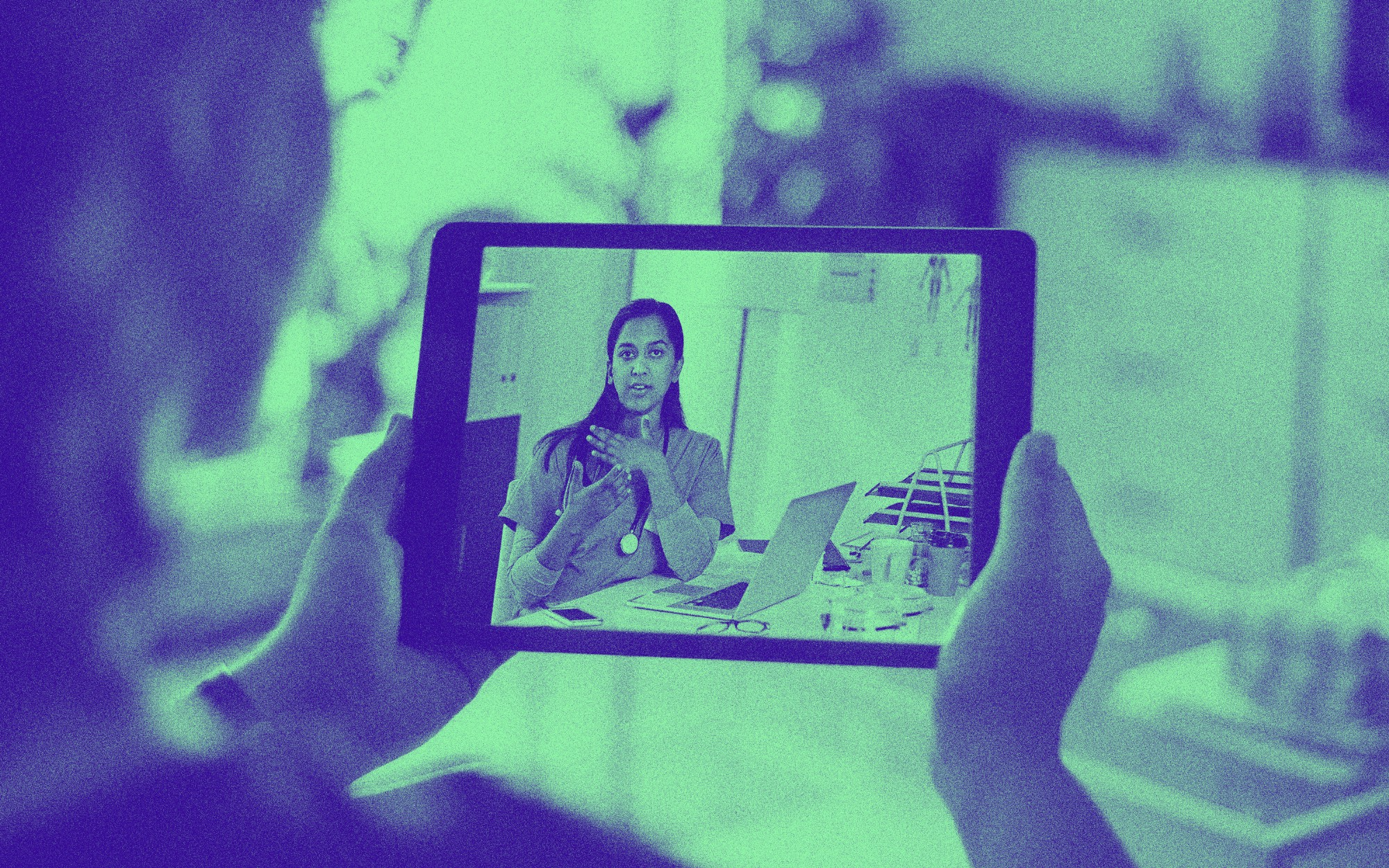 A woman holds up a digital tablet and talks to a doctor over teleconference.
