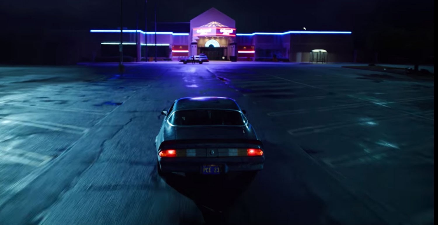 A still from the Stranger Things series on Netflix. A Camaro faces the Starcourt Mall in an empty parking lot at night.