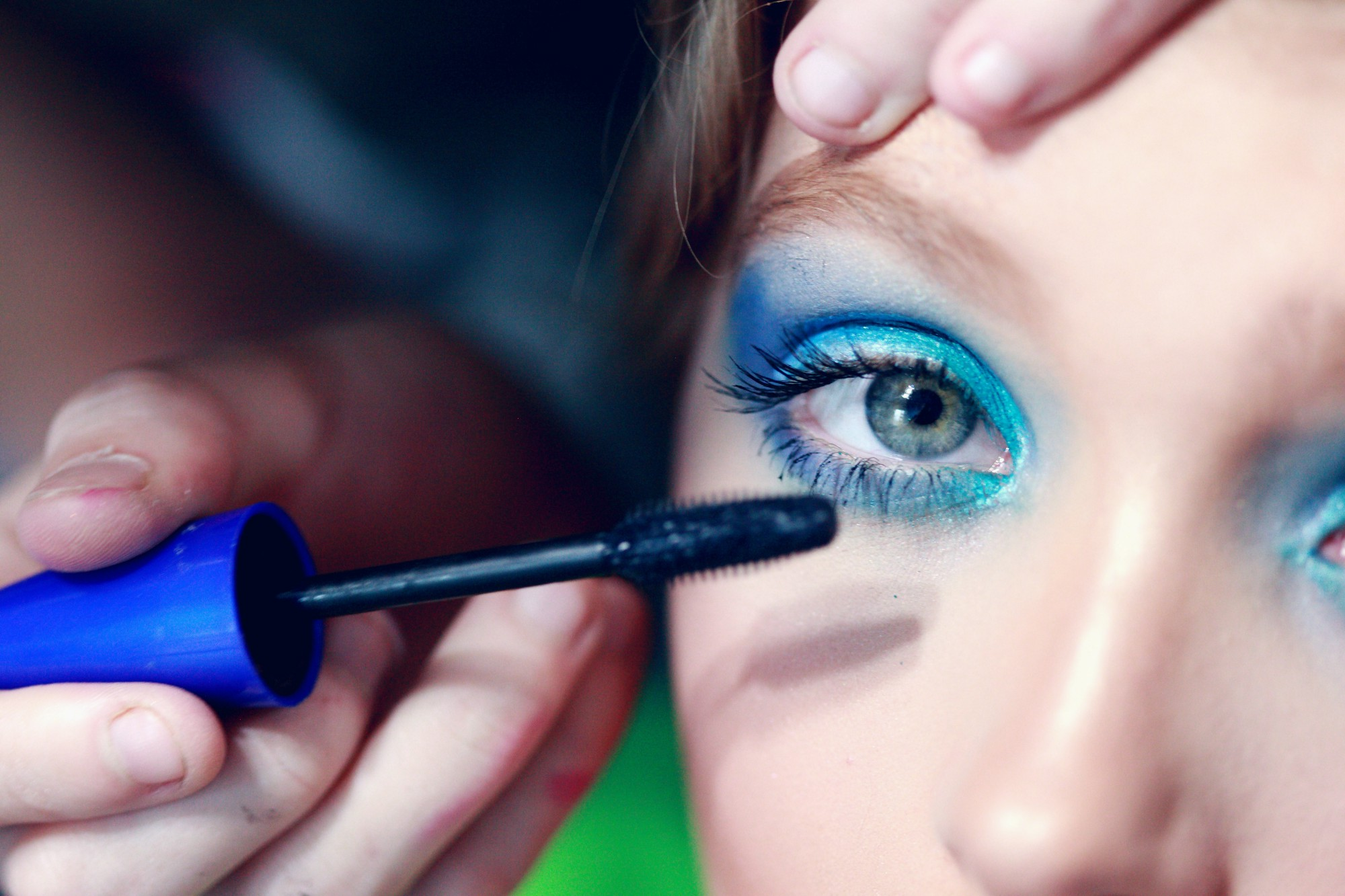 A blue mascara being applied to a woman's sad looking eyes.