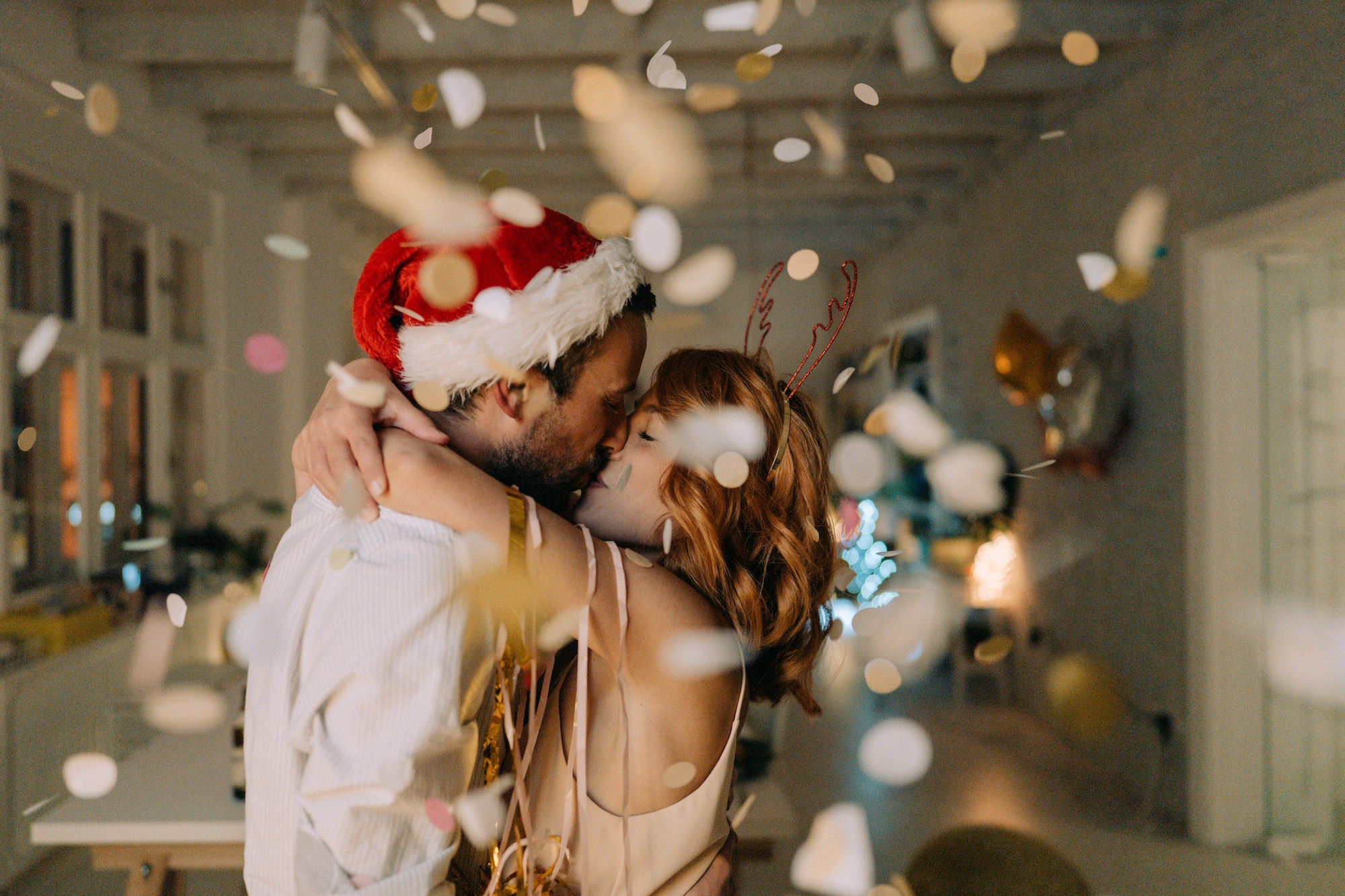 A young couple embrace and kiss with confetti fluttering around them. One has a Santa hat and the other, reindeer antlers.
