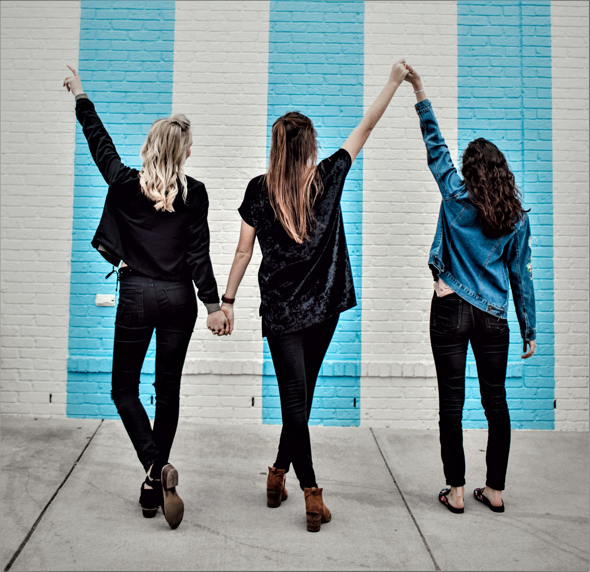 rear view of three girls facing blue and white stripe wall and holding hands