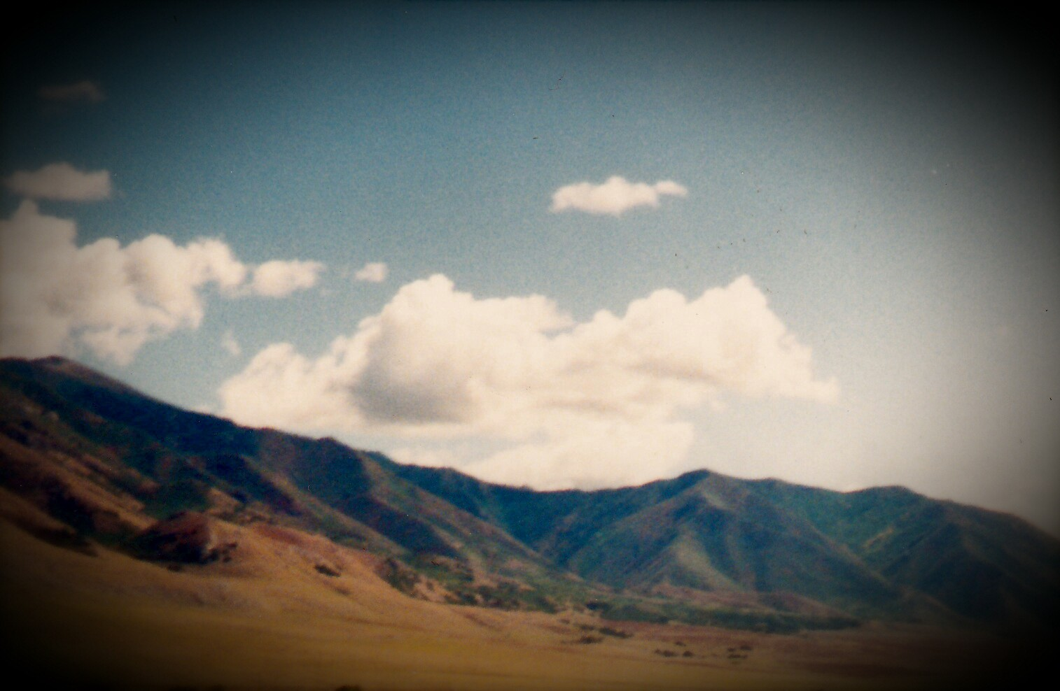 A vista of low mountains with blue sky and low white clouds.