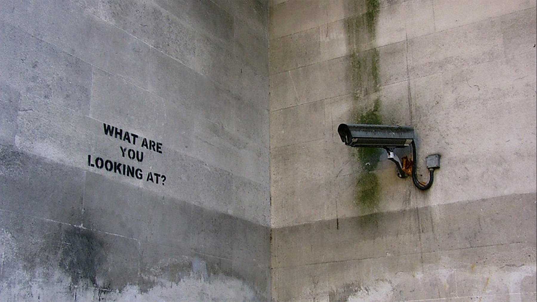 """Photo of Banksy's street art reading """"What are you looking at?"""" beside a CCTV camera on a concrete wall."""