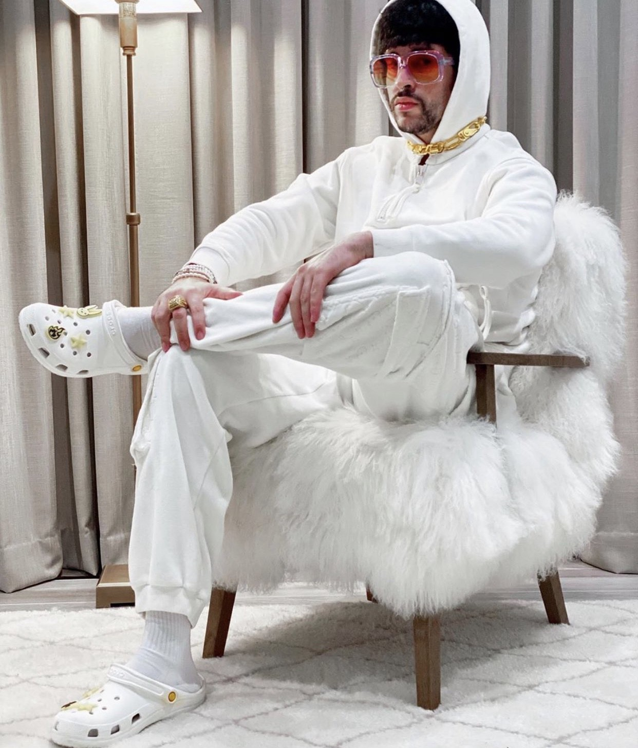 Puerto Rican singer rapper, Bad Bunny, sitting cross-legged on chair, dressed in all white and wearing white minimally bedazzled crocs
