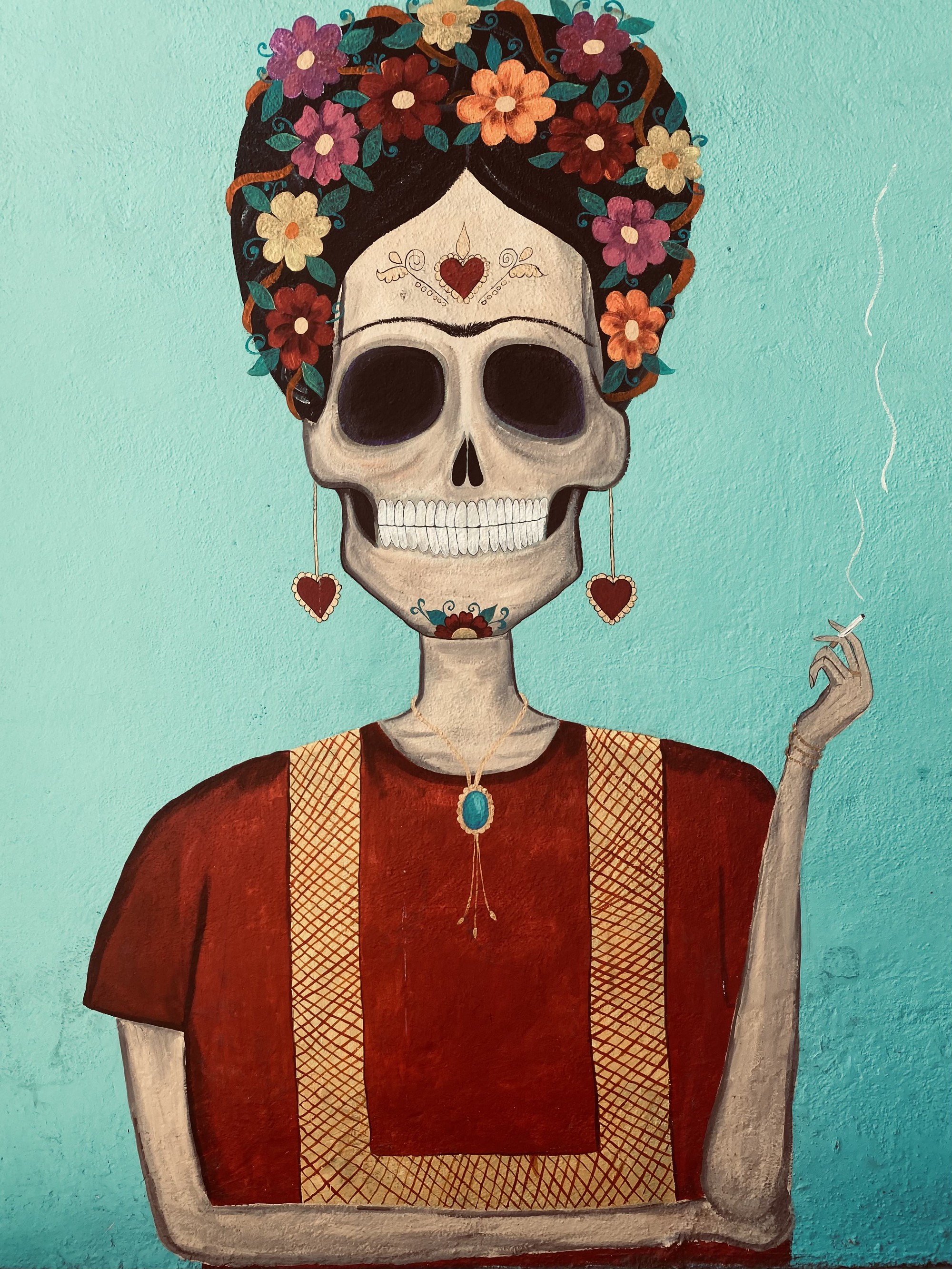 A mural on a blue wall. The mural depicts a sugar skull — a female-appearing skeleton covered in flowers and hearts. She is smoking a cigarette and grinning. Her unibrow suggests that she is Frida Khalo, or at least an homage to her.