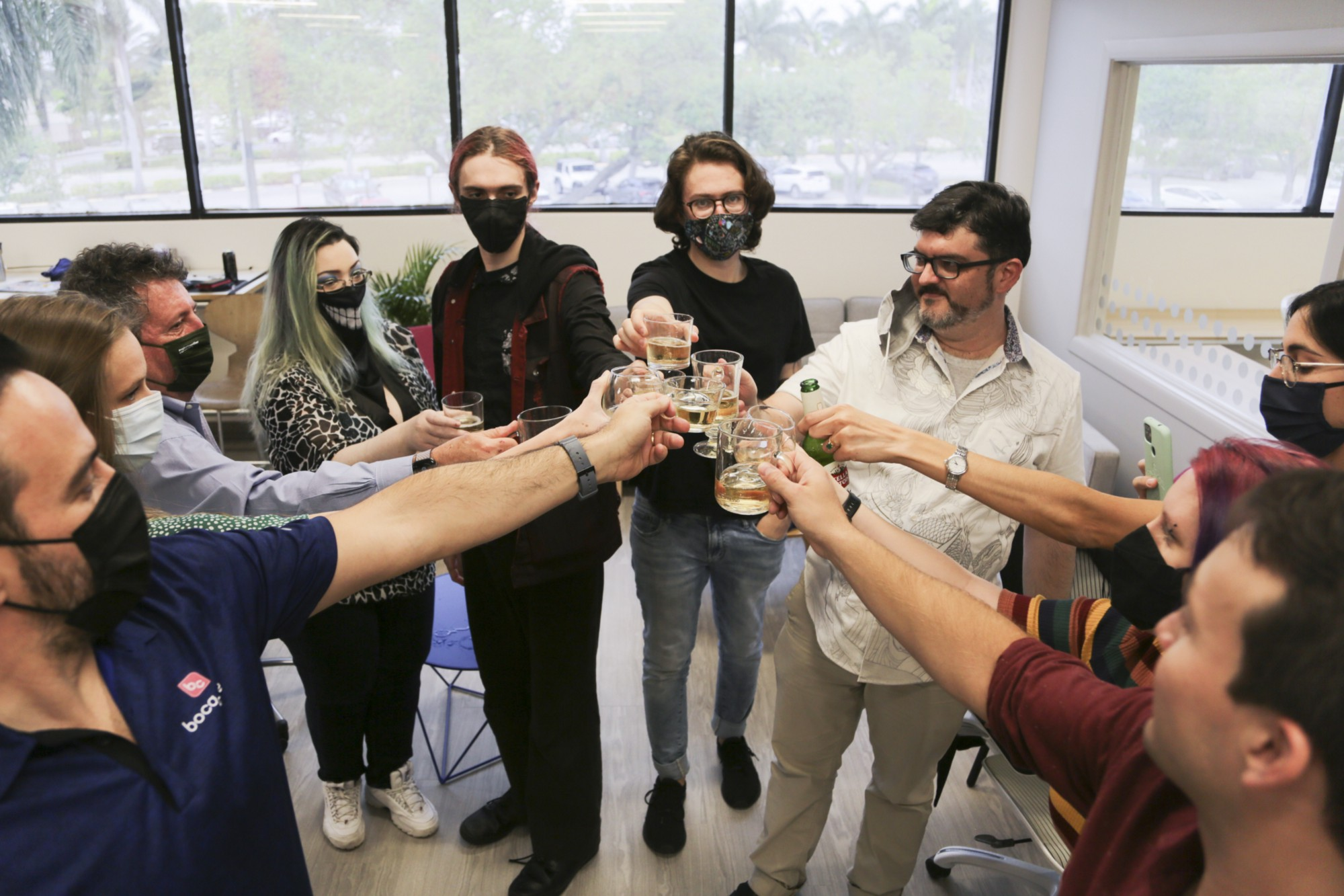 A group of 10 adults, students, instructors, and family, stand in a circle, glasses raised together, toasting to success.