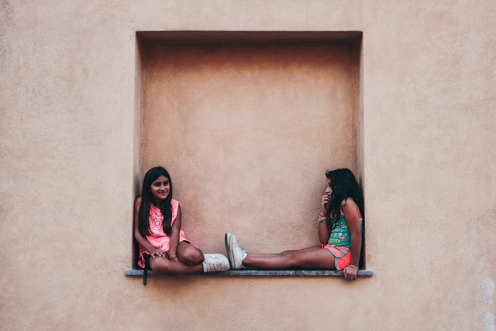 Two girls sitting in an alcove in a wall
