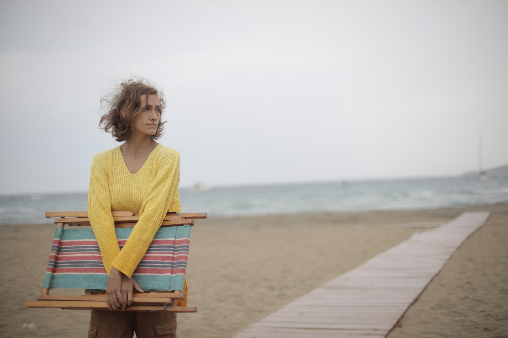 female traveler with beachchair looking wary on the beach