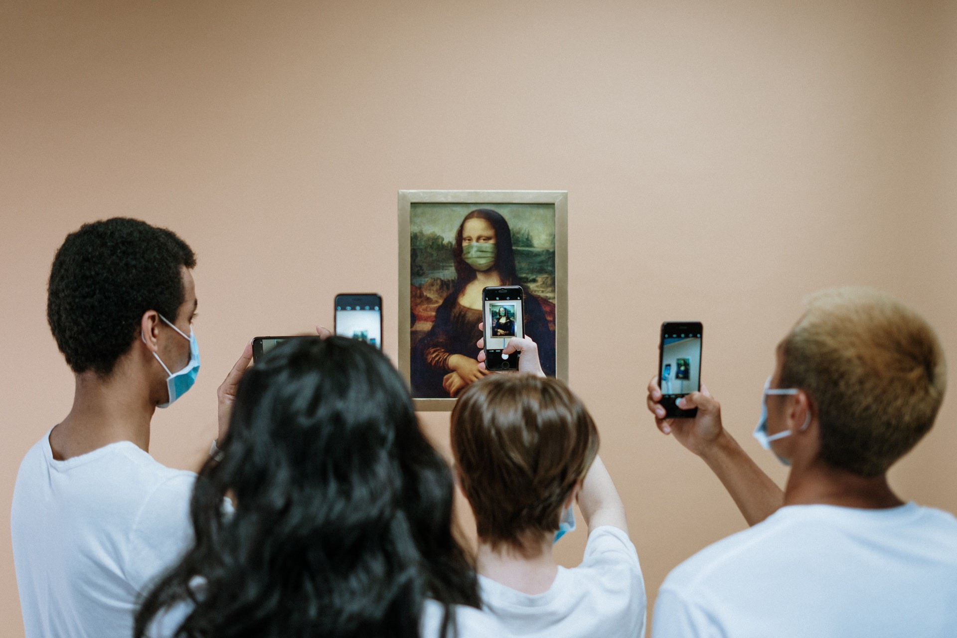 A group of people with medical masks takes a photo of a painting of the Mona Lisa, also wearing a medical mask.