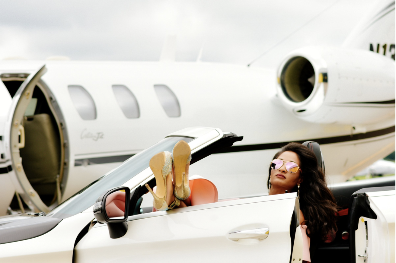 Luxury. Fabulous female pulled up in a fancy car next to her private jet ready to take on the day.