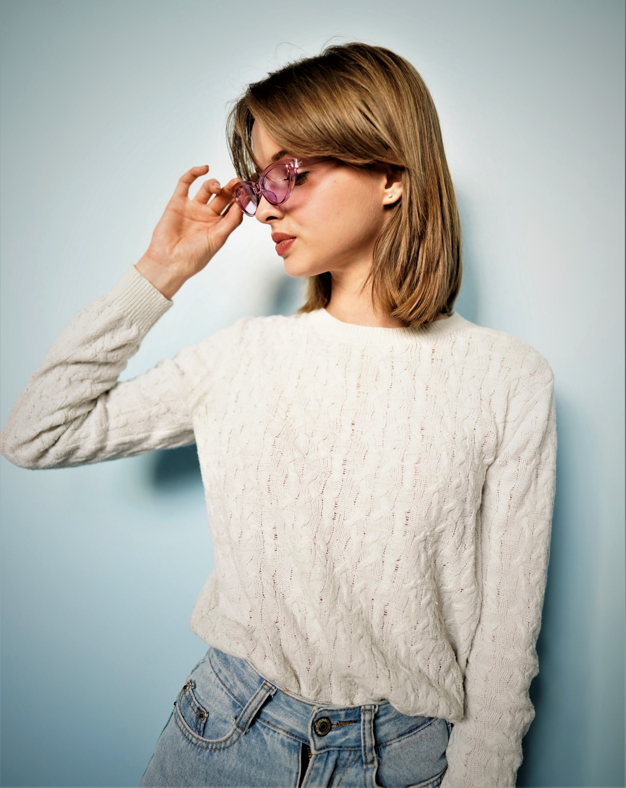 woman wearing long sleeve white sweater and glasses with head turned to profile and fingers touching glasses