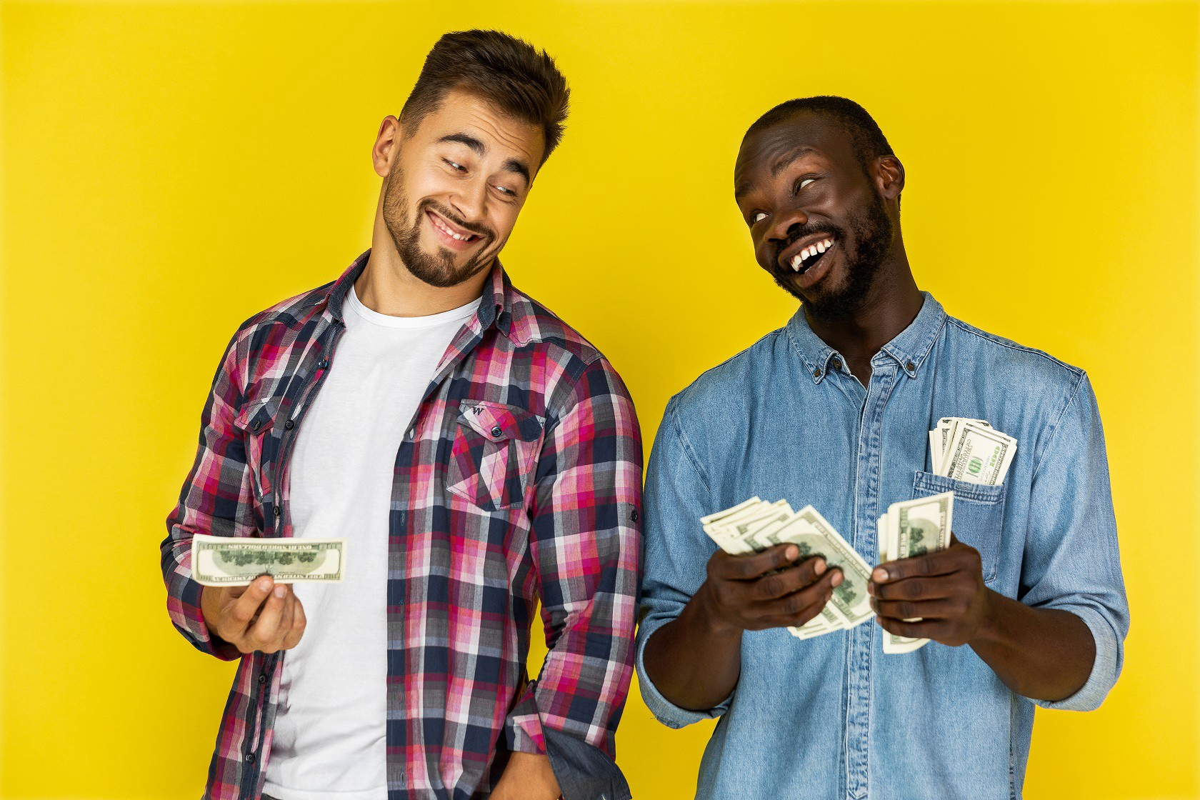 Two men smiling while holding money with a yellow background