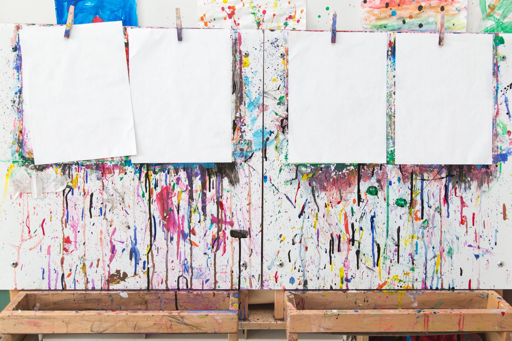 Four blank pages hang on paint covered easels in an elementary school classroom.