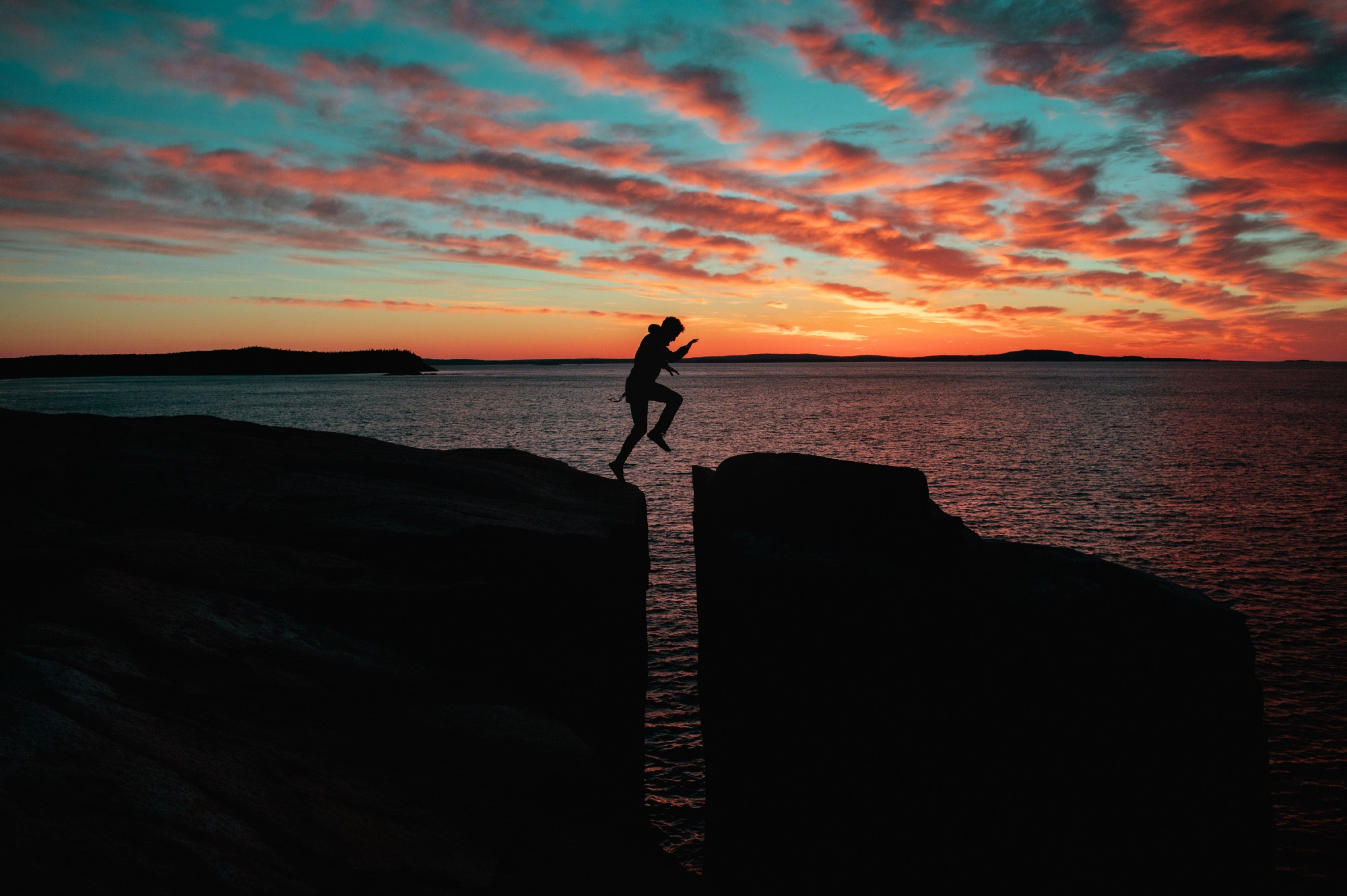 A silhouette of a person jumping over rocks at dusk.
