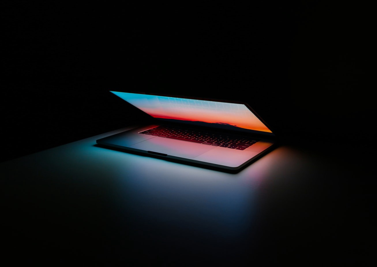 A closing laptop lid with ominous lighting.