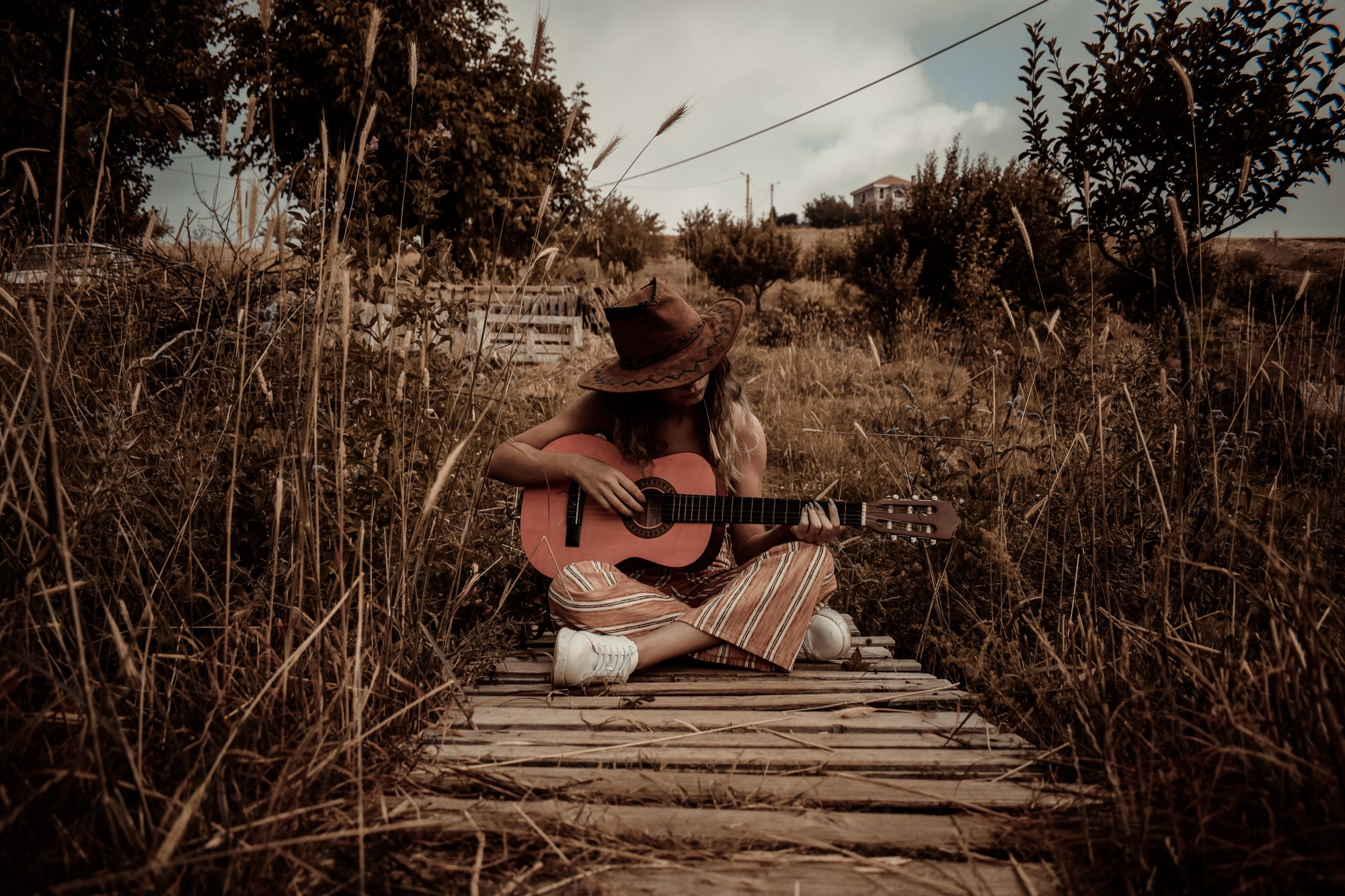 Woman sitting on ground playing guitar