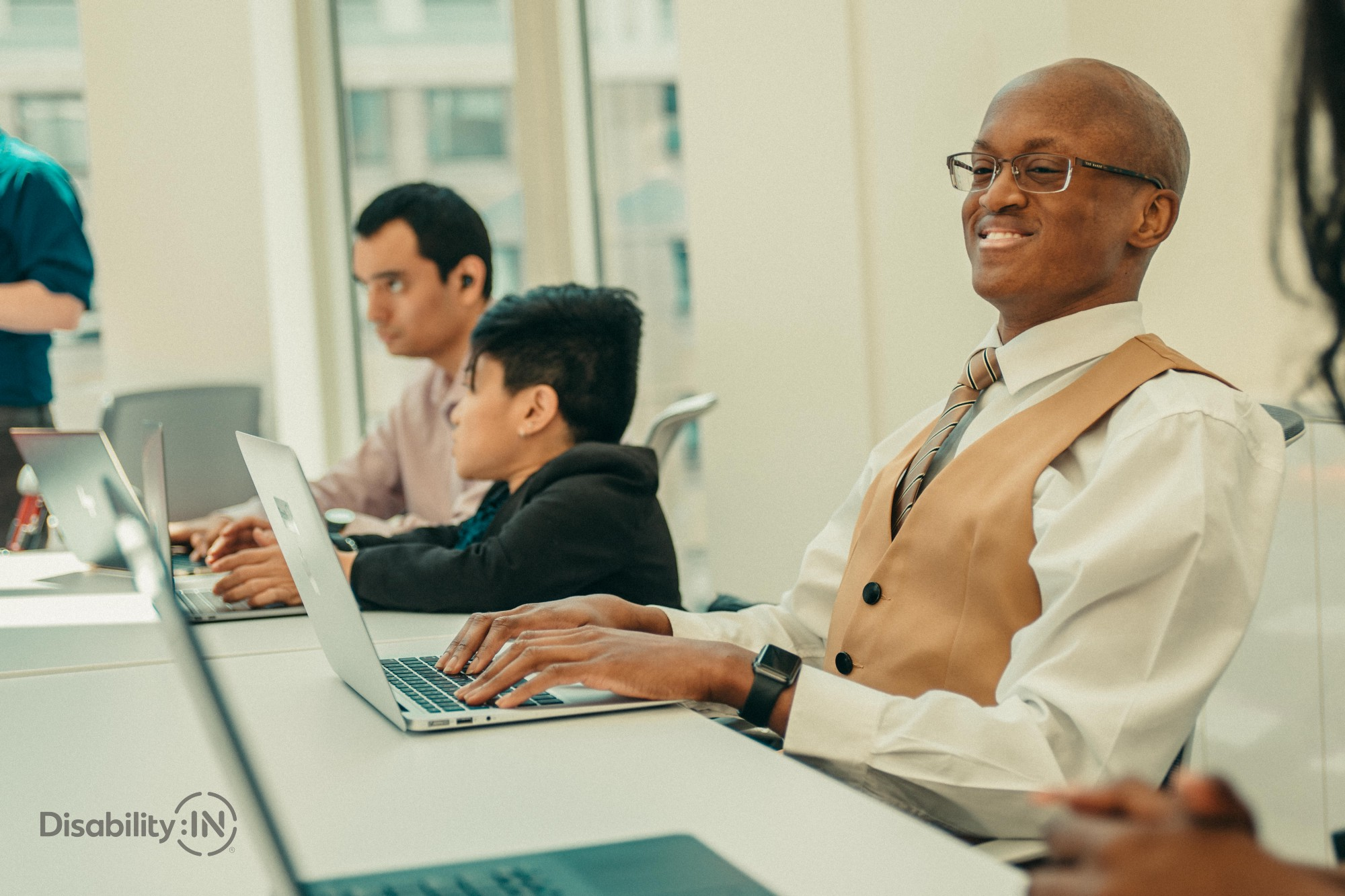 Smiling man with a learning disability works on a laptop in a meeting with other colleagues.