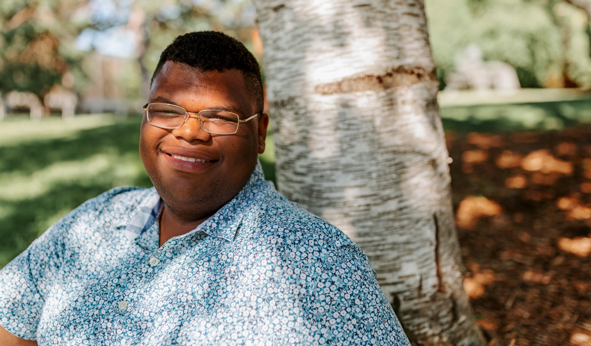 Jayven smiles as he rests in the shade against a tree