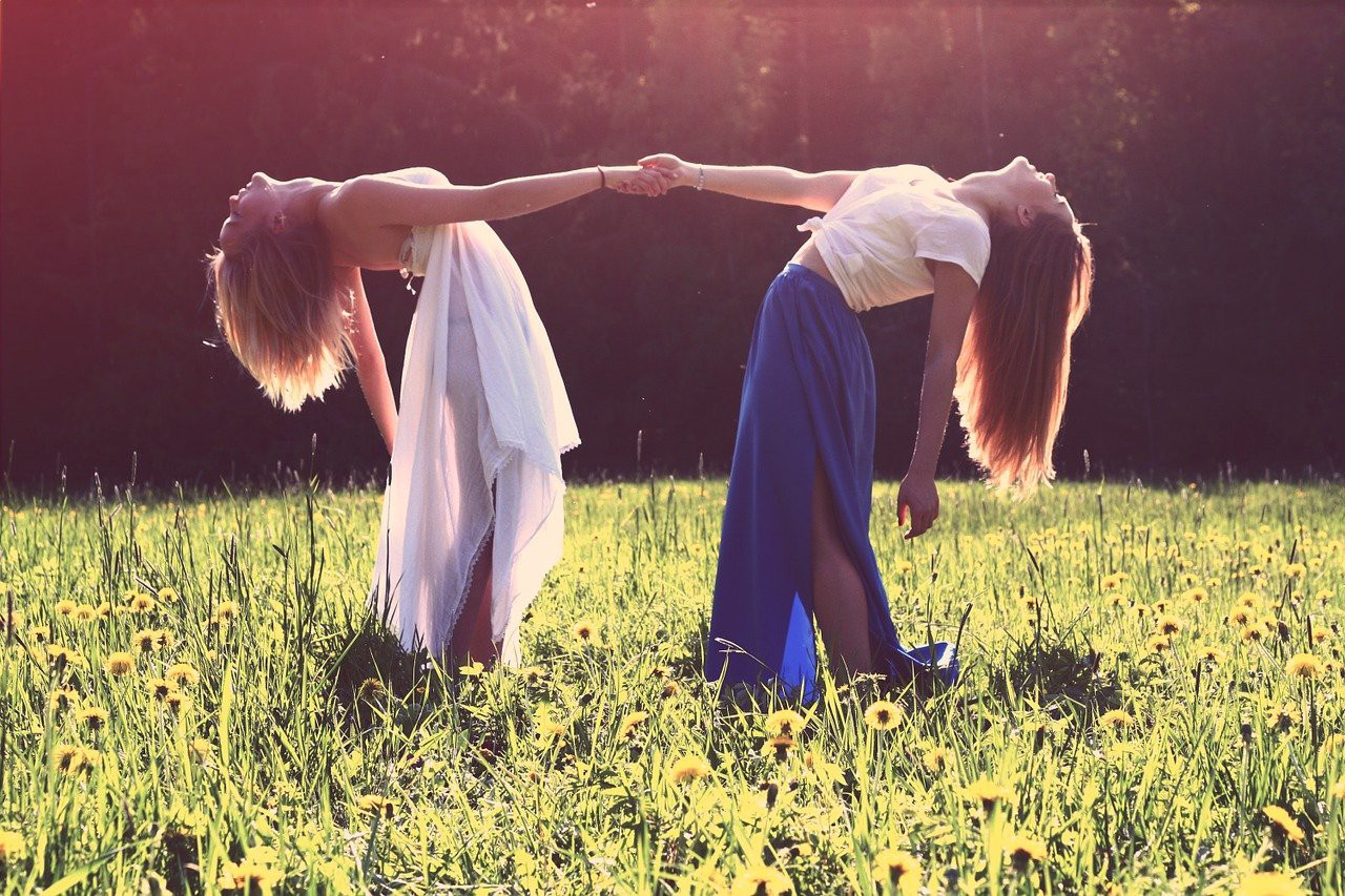 two women in the sun holding hands with heads thrown back in joy