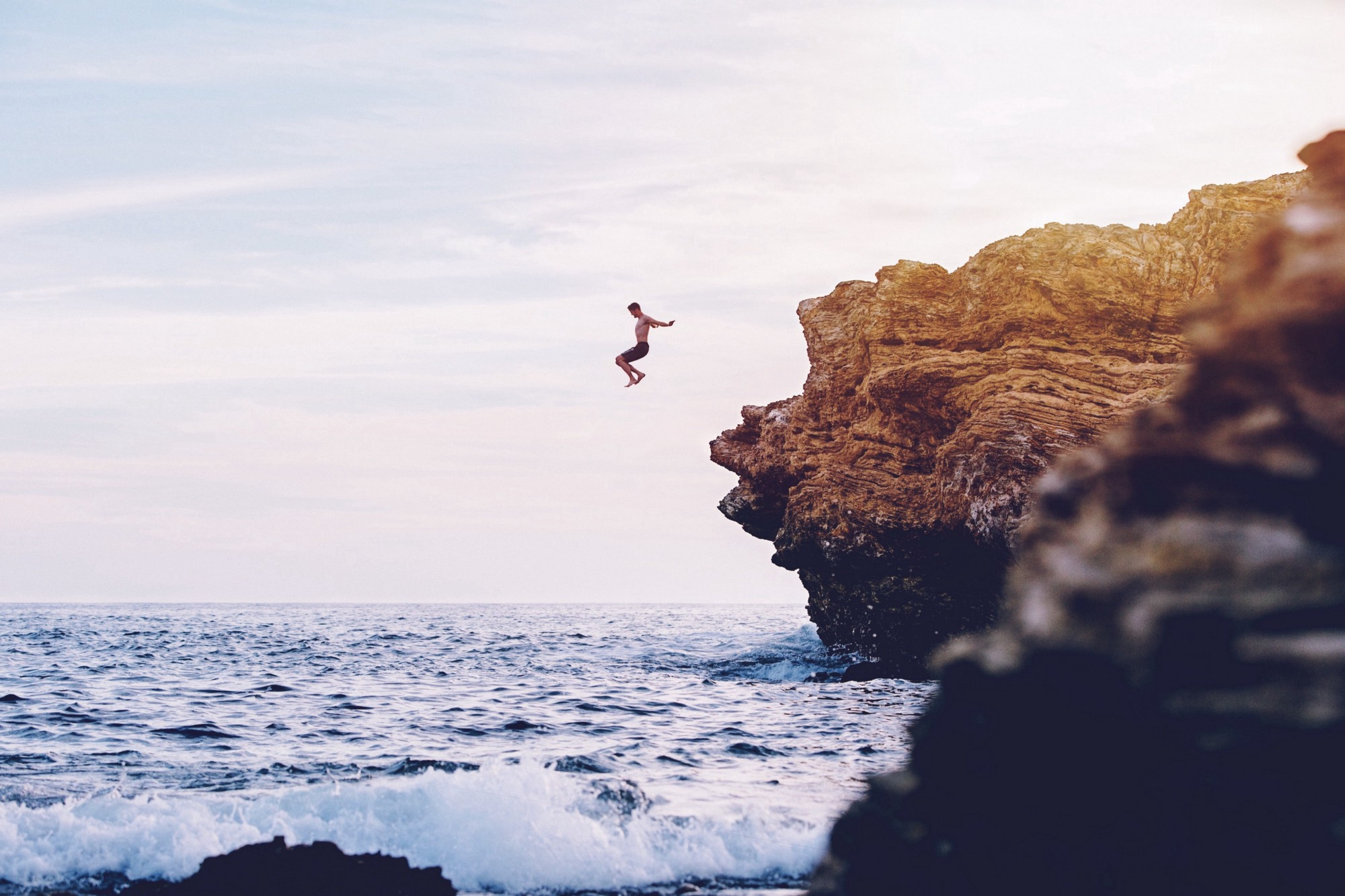 a brave man jumps from a tall cliff into the ocean