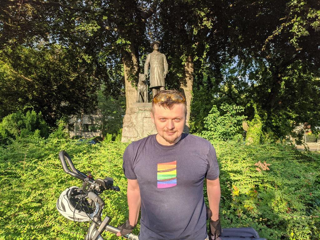 A photo of the author in front of a statue of Otto von Bismark with his dog. Bismarckplatz, Berlin, Germany.