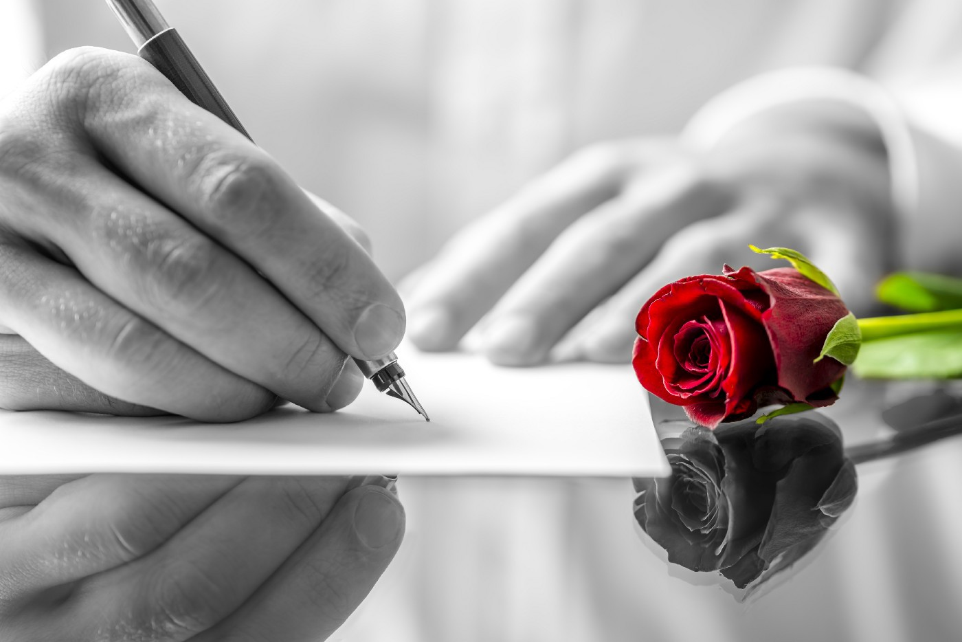 An image of a hand writing a letter