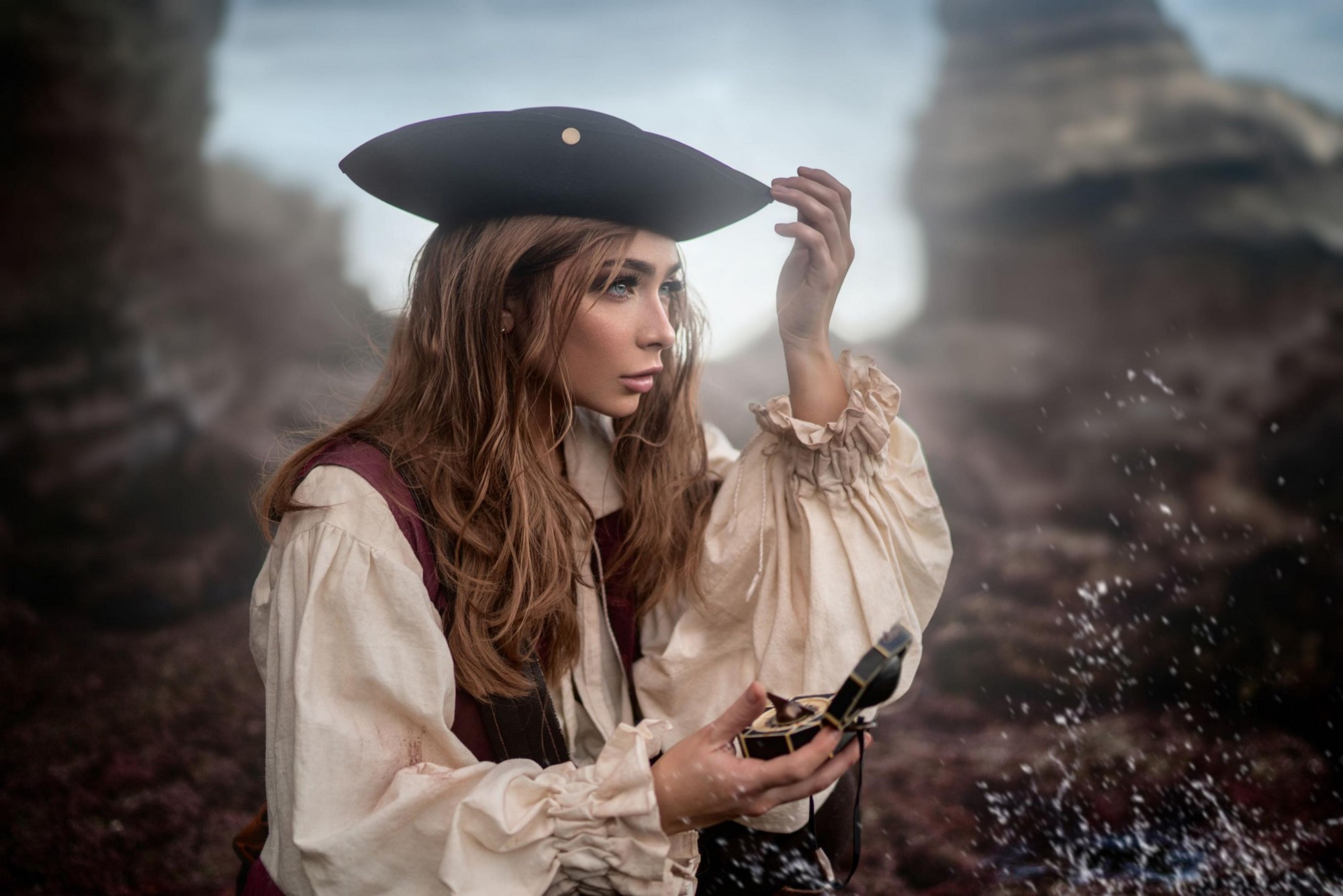 A woman in a pirate outfit holding a compass near a beach cave.