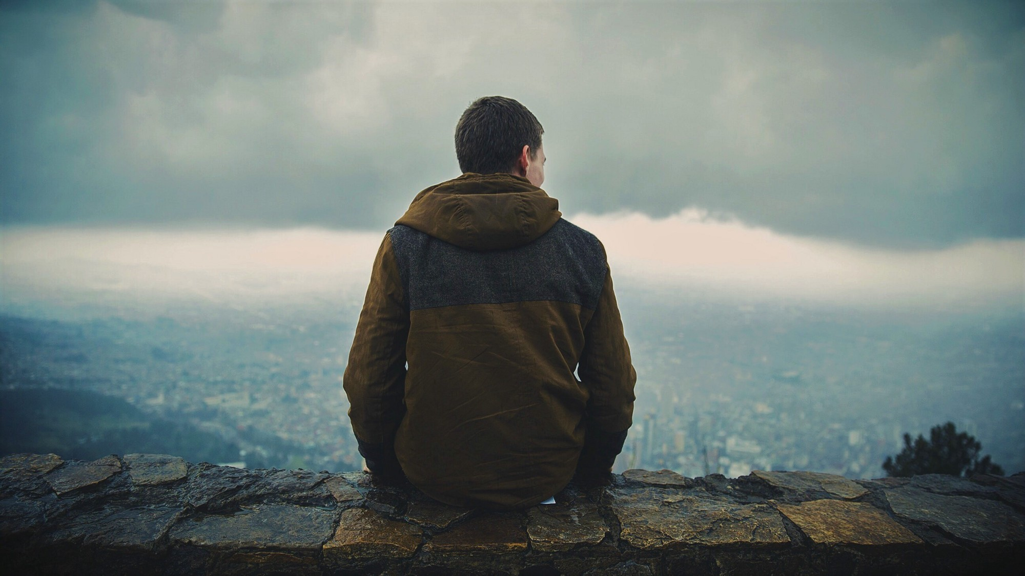 man in hooded jacket sitting on stone wall looking out over landscape and stormy sky
