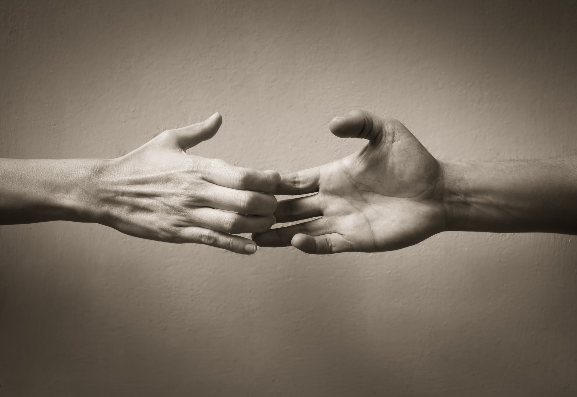 A black and white image of two hands pulling apart, as if there were until just now holding each other but now drift apart.