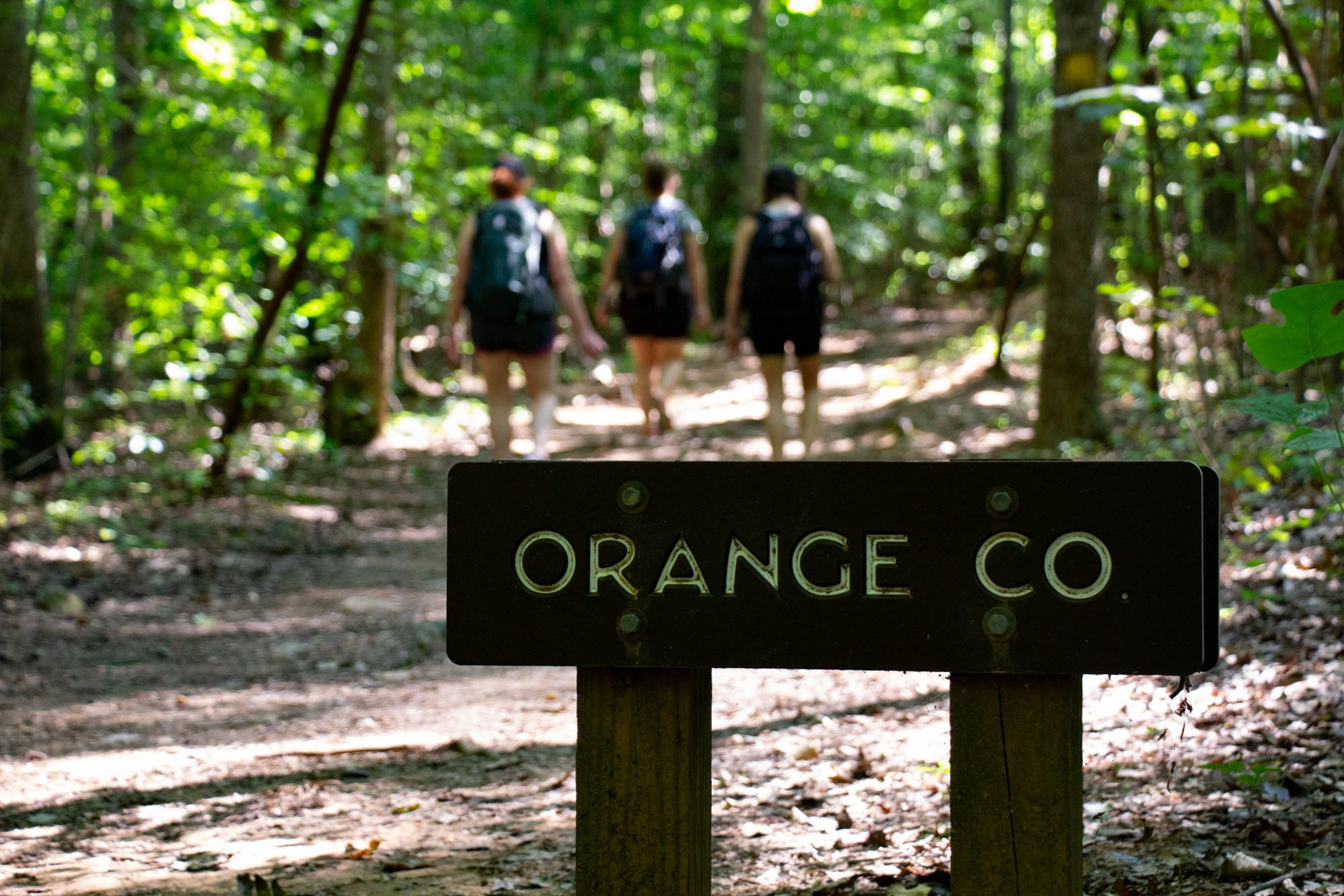 """The NC State Park-sanctioned sign """"Orange County"""" designating the line in the trail between Durham and Orange counties."""