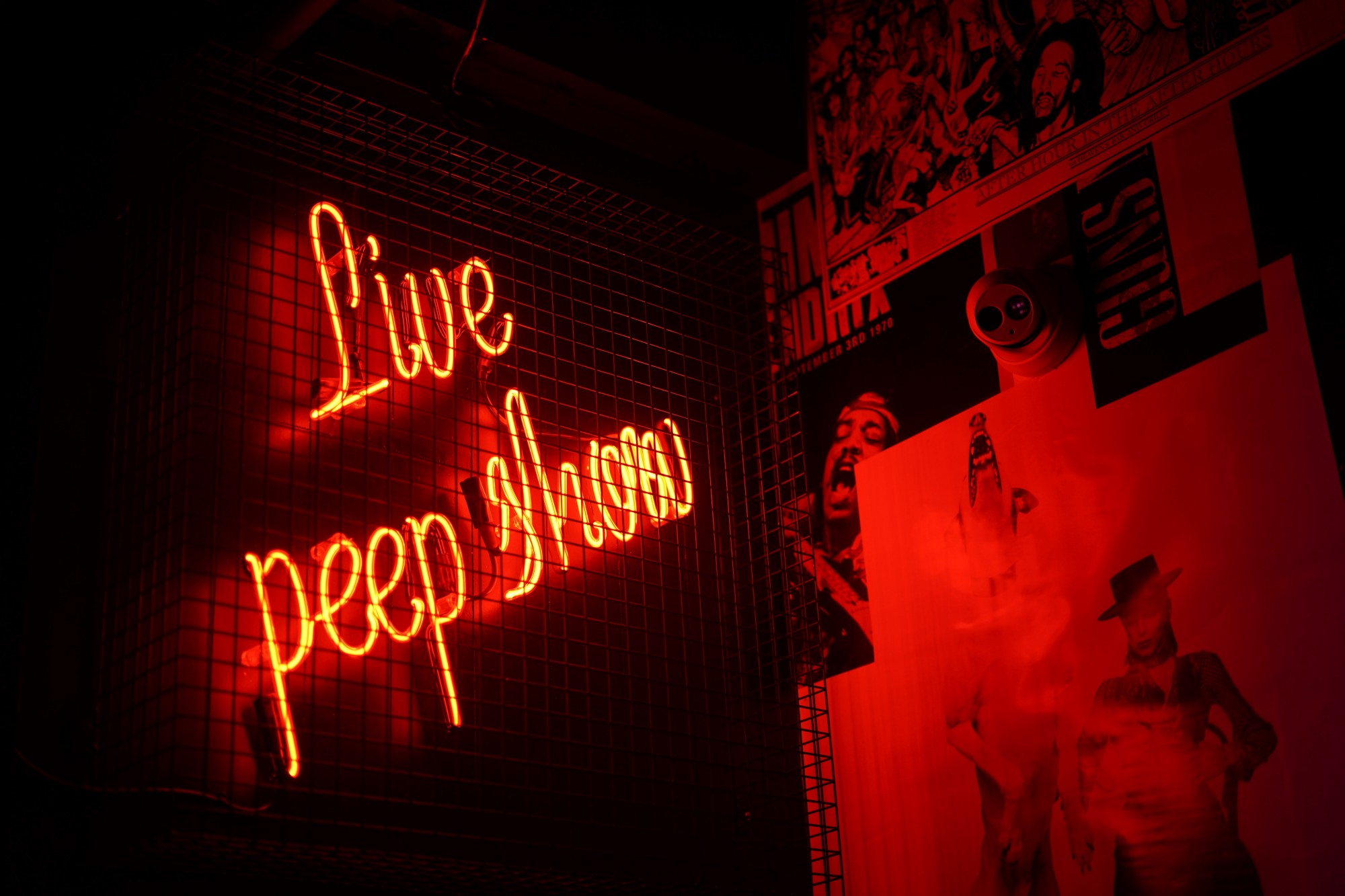 """red neon sign reading """"live peep show"""""""