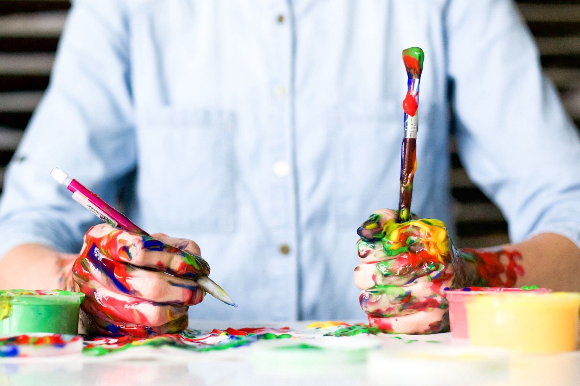 A person painting with a few colorful brushes.