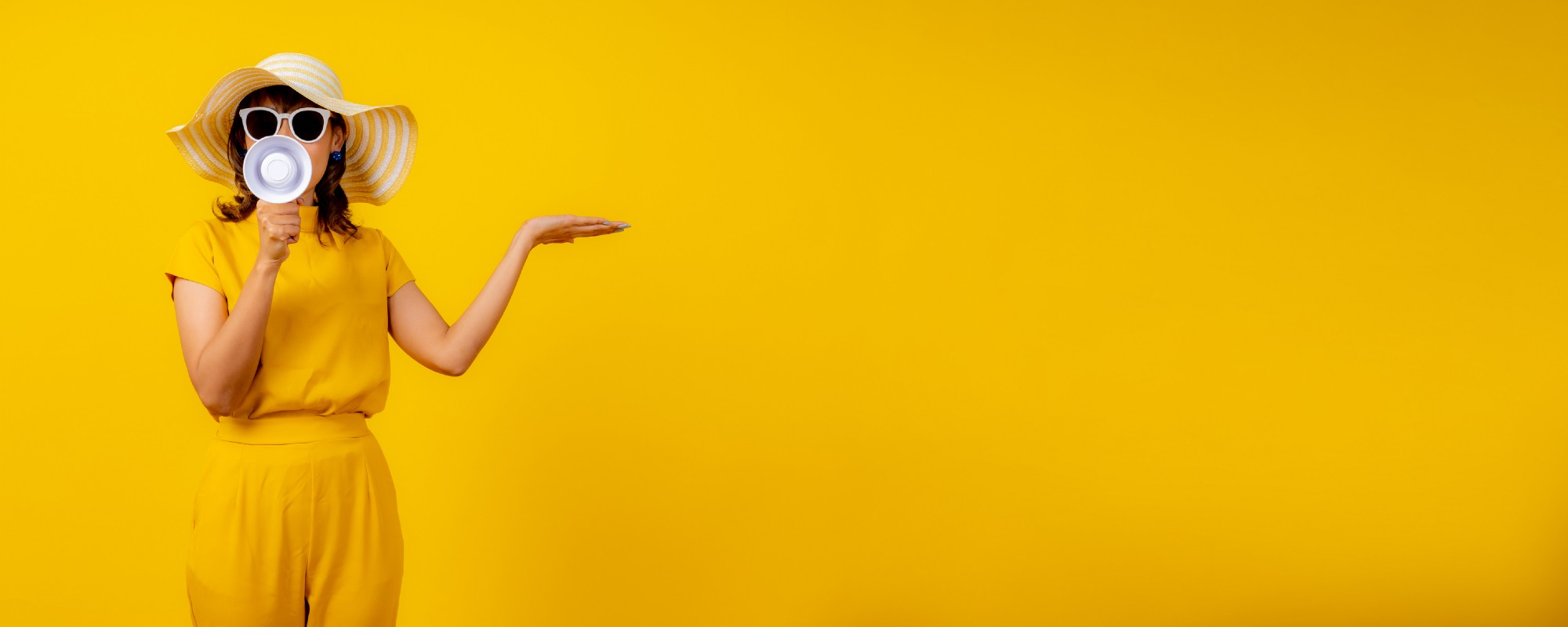 A lady with a handheld loudspeaker against a yellow background