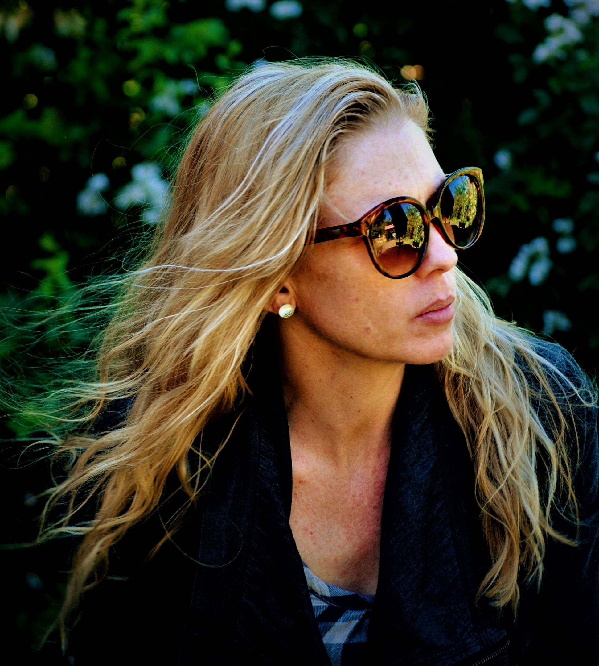 concerned woman with long blonde hair wearing sunglasses and dark jacket against green foliage background