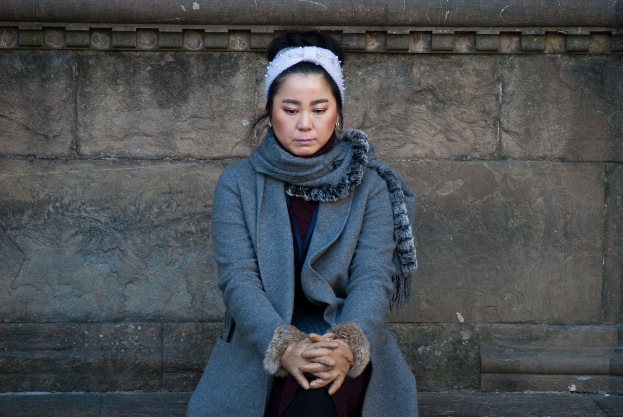 A woman sits quietly next to a stone wall with hands folded and eyes downcast