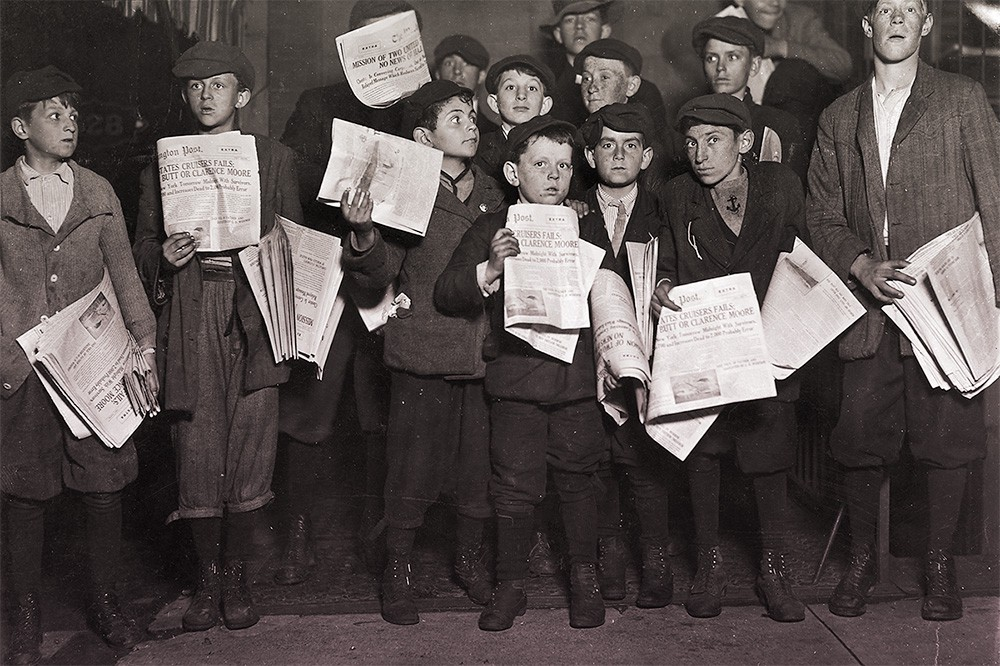 Newsboys holding up their papers for sale, dressed in black caps, jackets, knickers, socks, and boots.