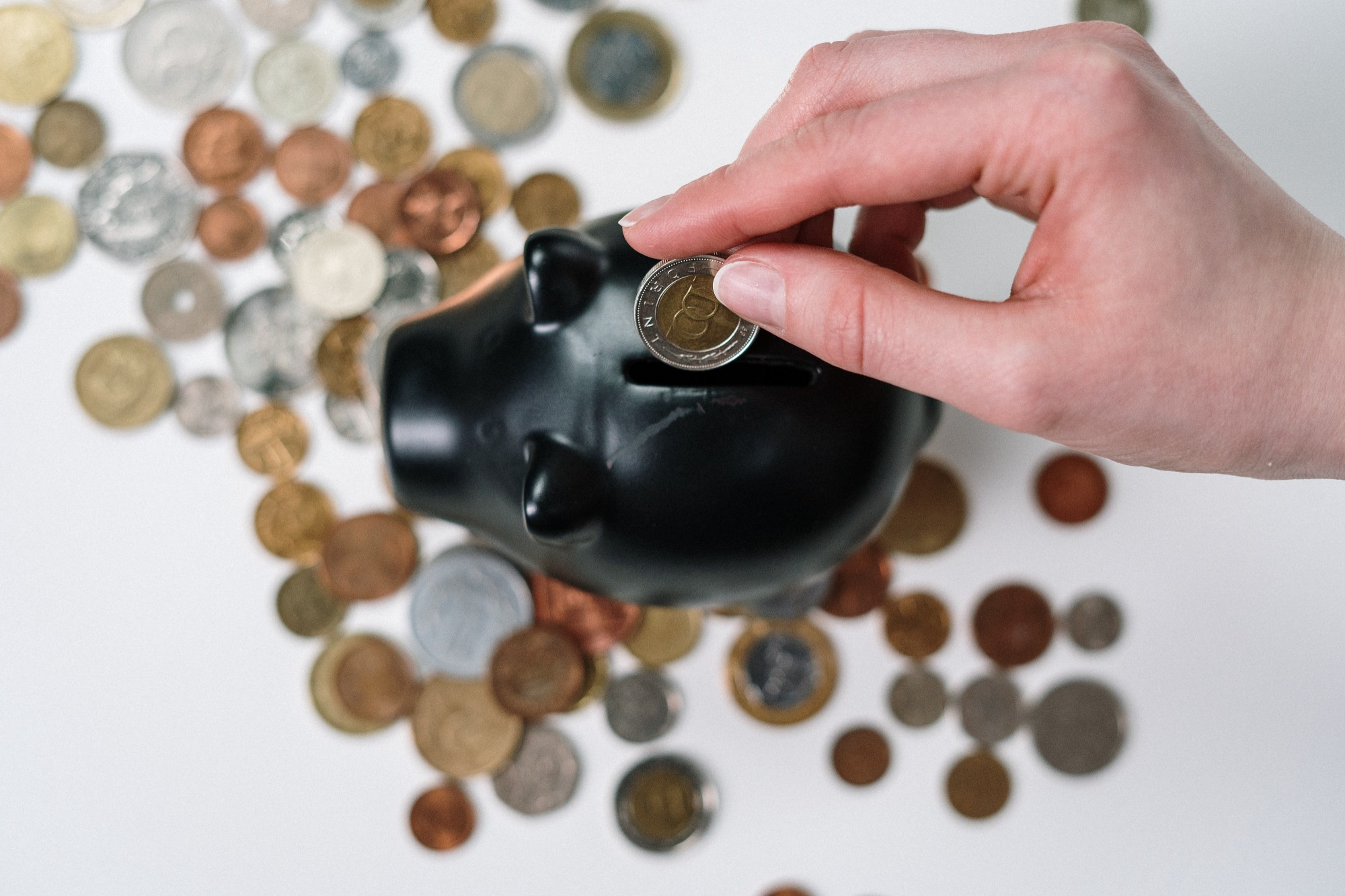 Person putting a coin in a piggy bank.